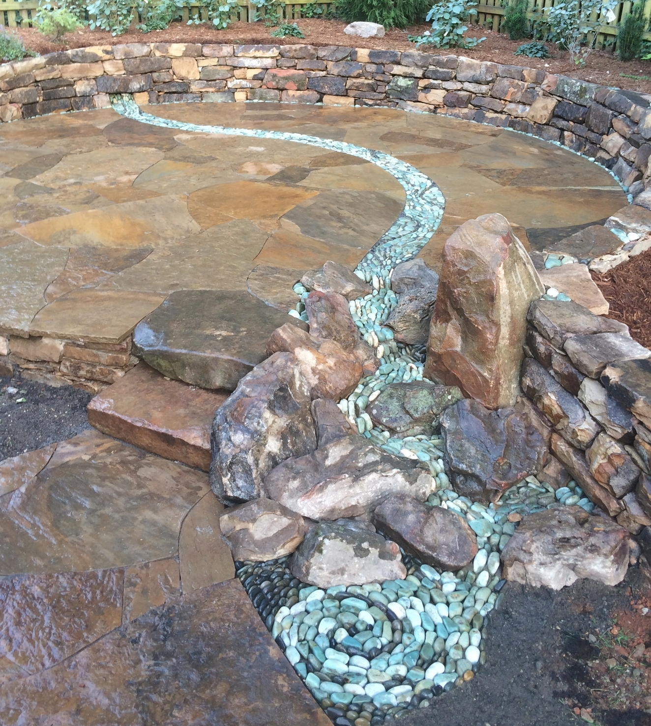Dry stream winding through a dry laid patio with waterfall and eddy pool