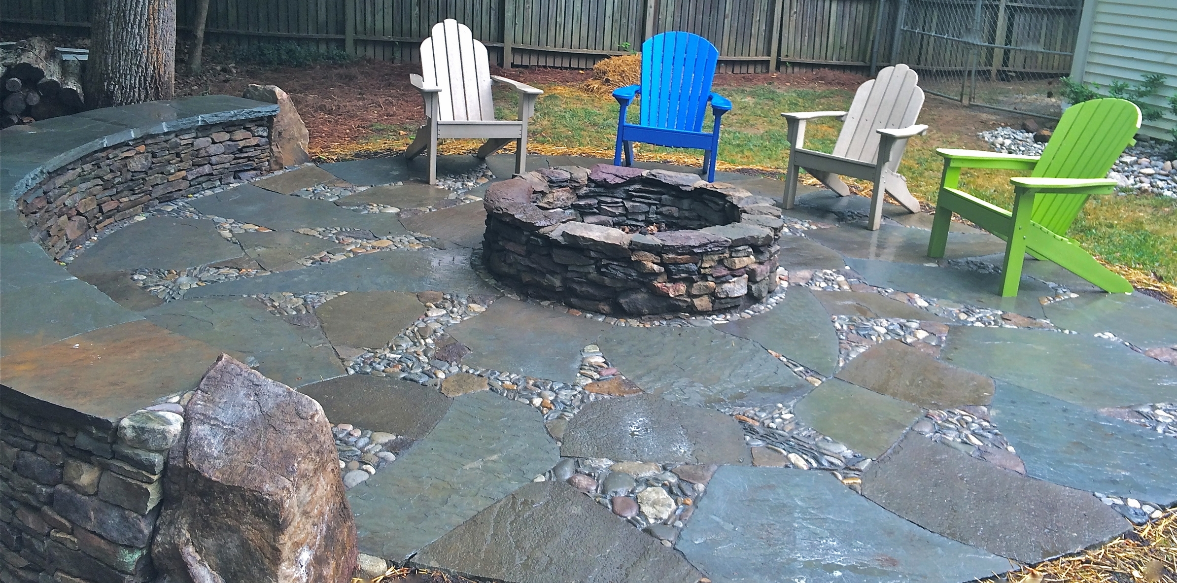Dry laid flagstone patio and wall surround an existing fire pit
