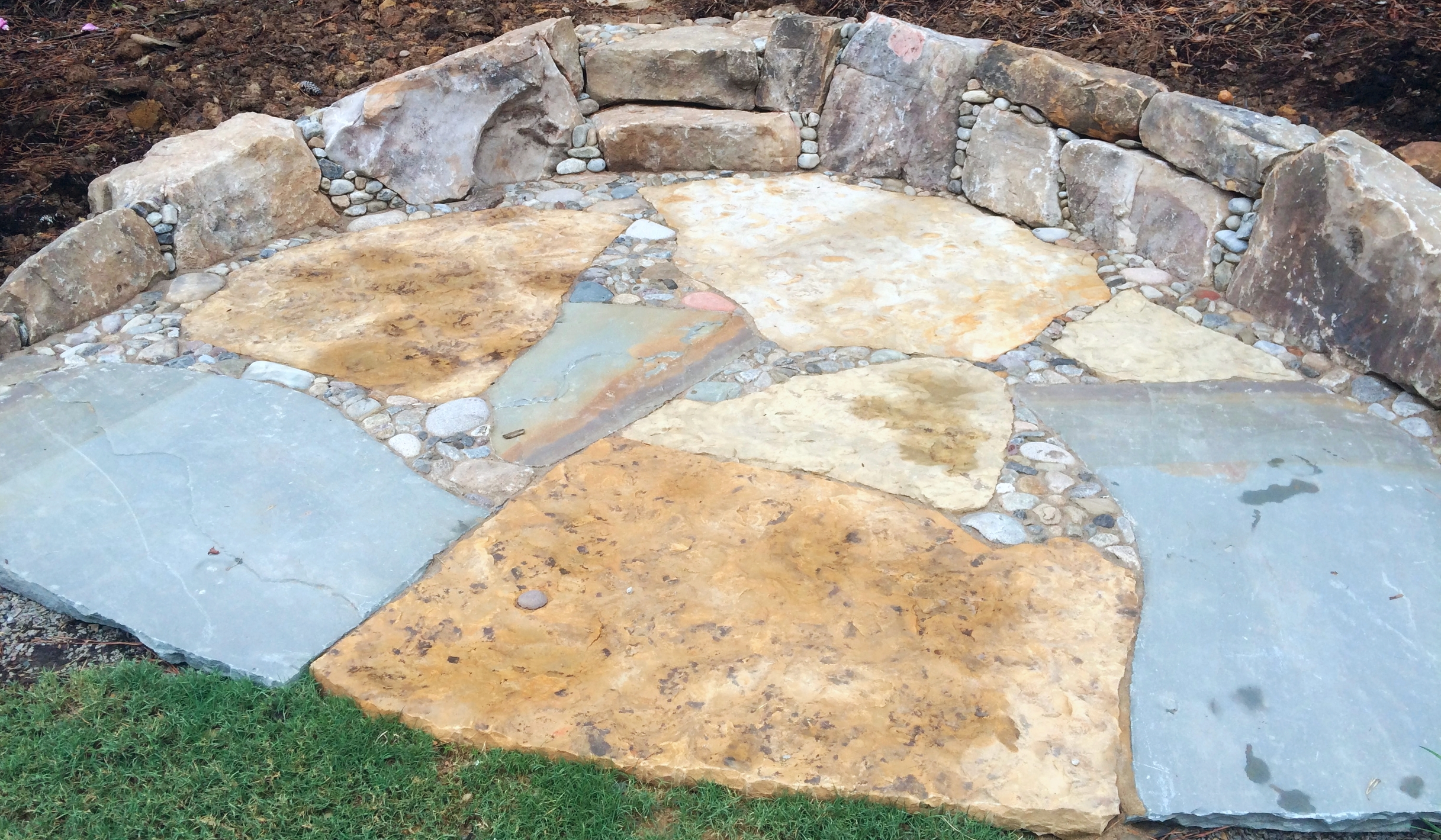 Pebbles enhance large boulders and flagstone to create a backyard sitting area