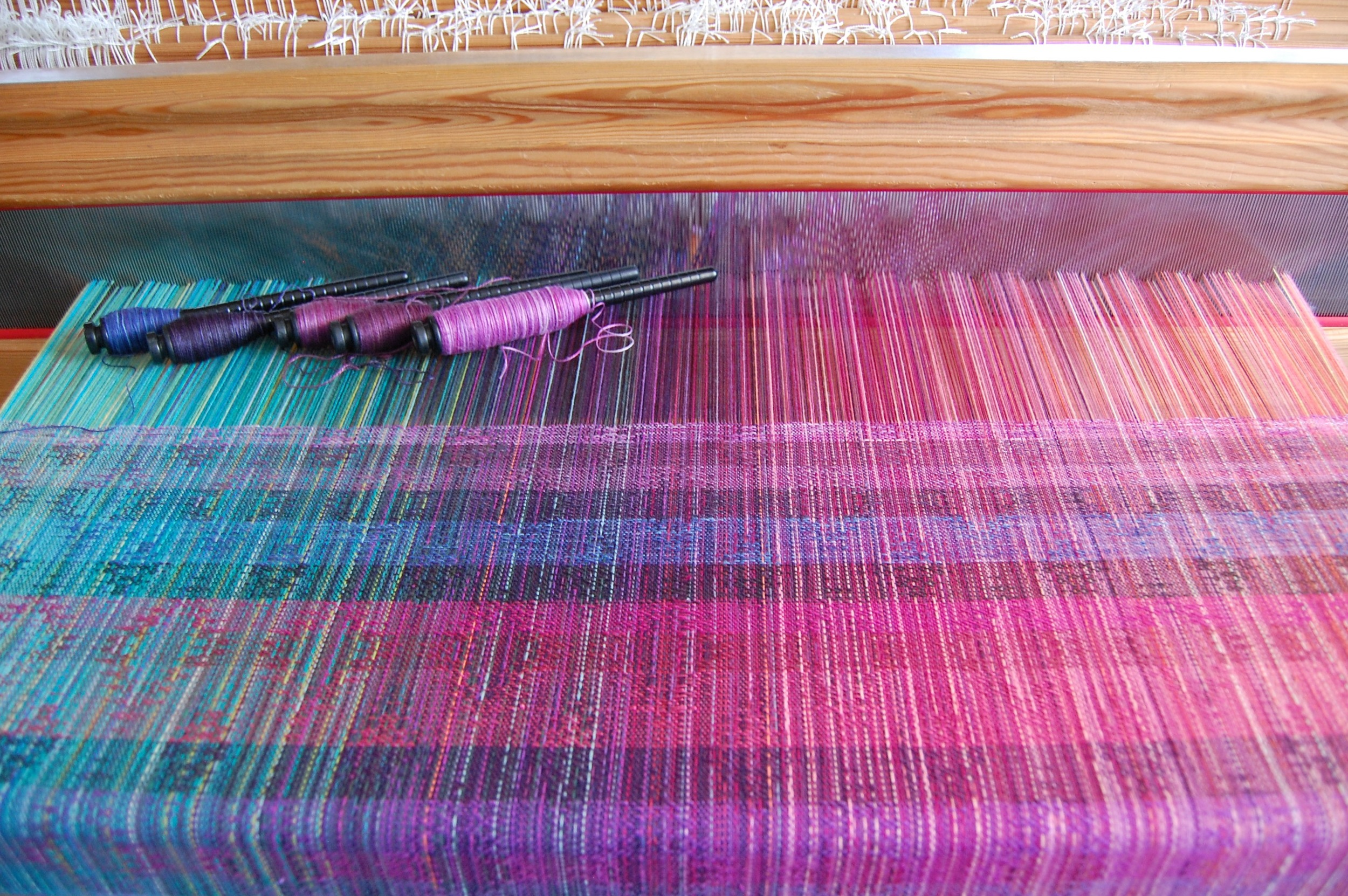Variegated weft yarns (top five stripes). The bottom stripe corresponds with the left-most pern: 40% hemp/60% cotton in blues and purples, madeline tosh superwash lace merino in Clematis, 70% silk/30% sea cell in Amethyst, Phydeaux 80% superfine merino wool/20% silk in Pomegranate, 40% hemp/60% cotton in pinks and purples.