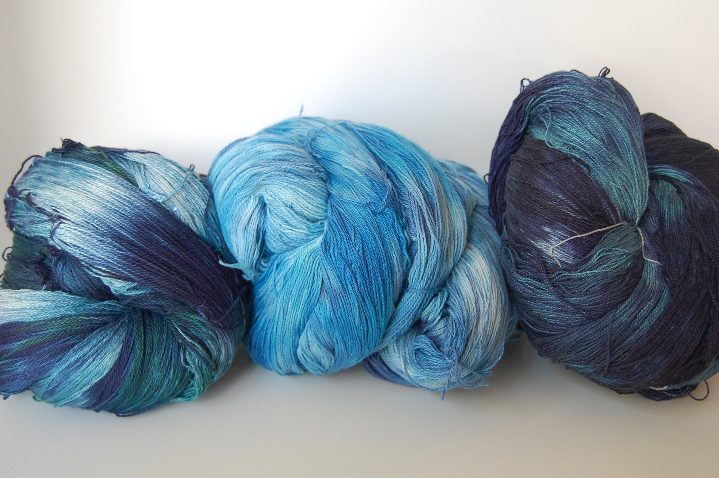 three hand-dyed wefts. at left is Organic pima cotton and is an early attempt at smoothly variegated color. center is the same technique after some more practice. at right is an acid-dyed silk weft.