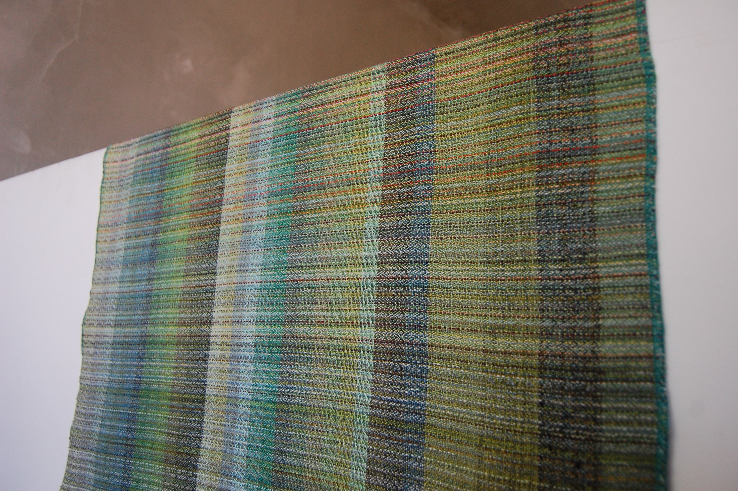 The weft sample piece - wet finished. Cottolin colors are shown on the left from light green to dark green; cotton colors are shown in the middle from light green to dark green; special fibers are the 4 wider stripes on the right.