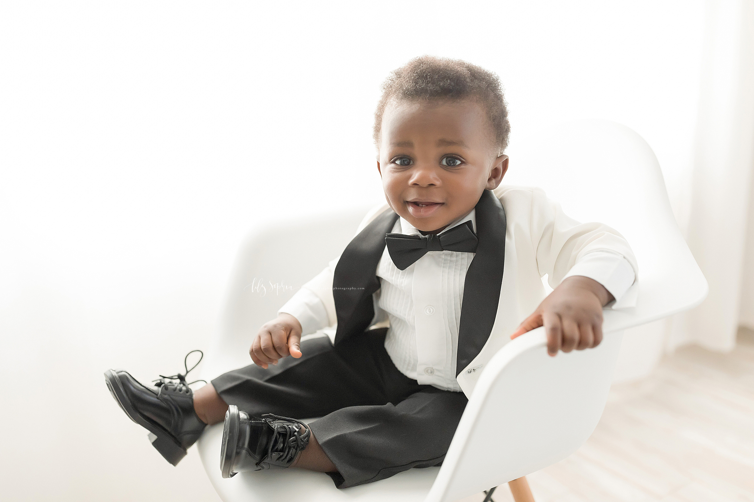 Photograph of an African-American little boy sitting in a molded white chair in a tuxedo.  The little boy is wearing black pants, black oxford shoes, and a white tuxedo jacket with black accents.  He is holding the chair with his left hand and is smiling.