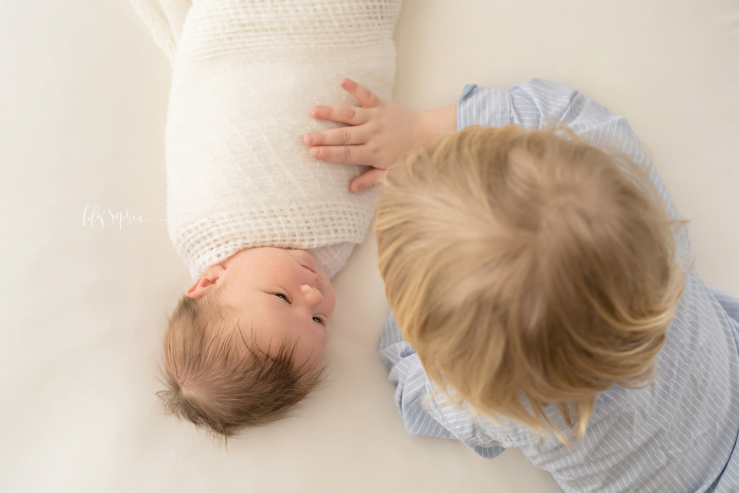 Aerial image of two brothers. The older blonde haired brother is putting his hand on his brown haired newborn brother who is wrapped in a soft swaddle blanket.  The infant is looking up with bright eyes at his brother.