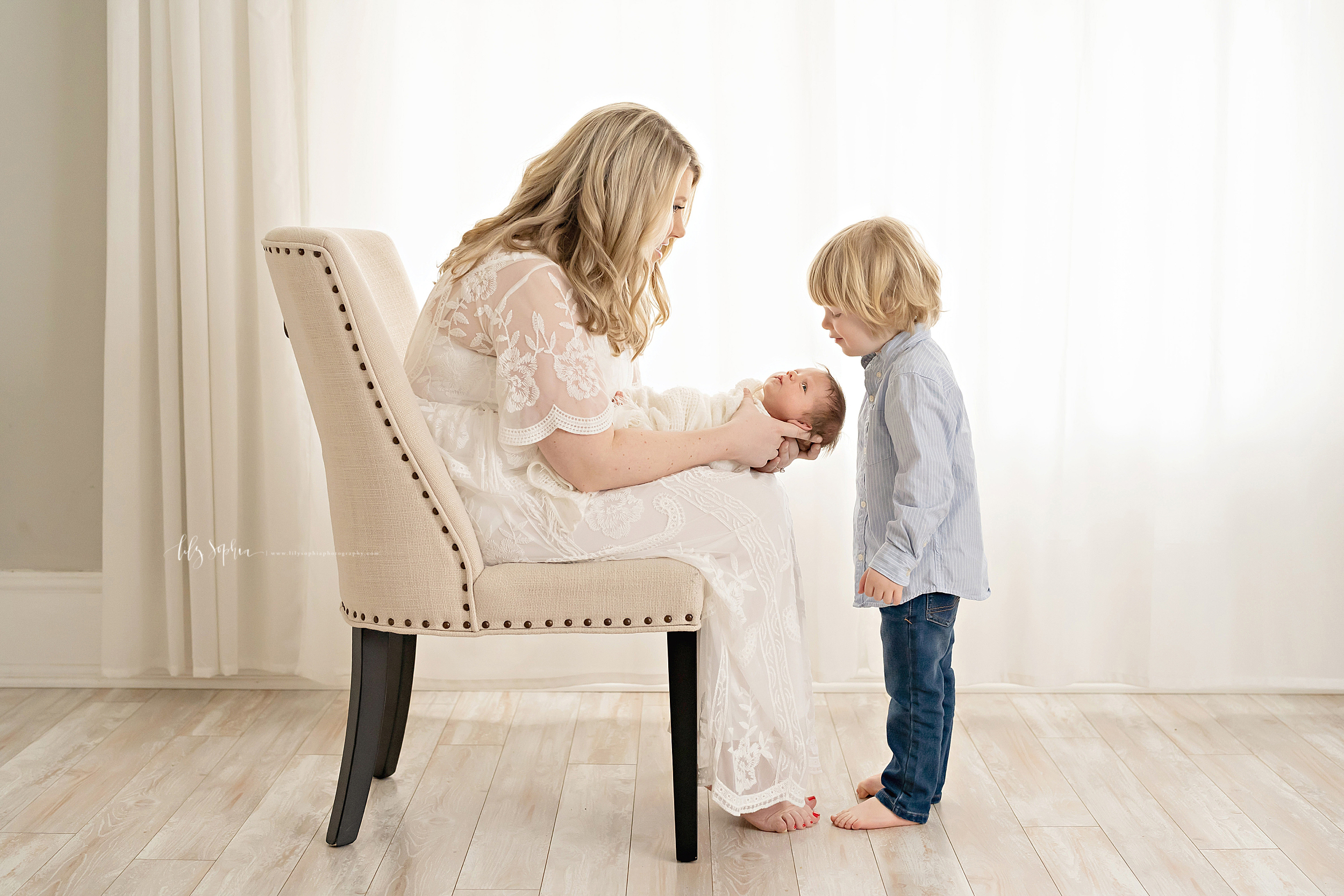 In an Atlanta natural light studio a mom sits in a nail trimmed cream linen chair with her infant son on her lap and her toddler son looking at his new brother. Mom is wearing a shear white embroidered full-length dress with scalloped short sleeves. Her infant is swaddled in a soft white blanket. Her toddler son is wearing a light blue long-sleeved buttoned-down shirt and blue jeans. Mom and son are barefoot.