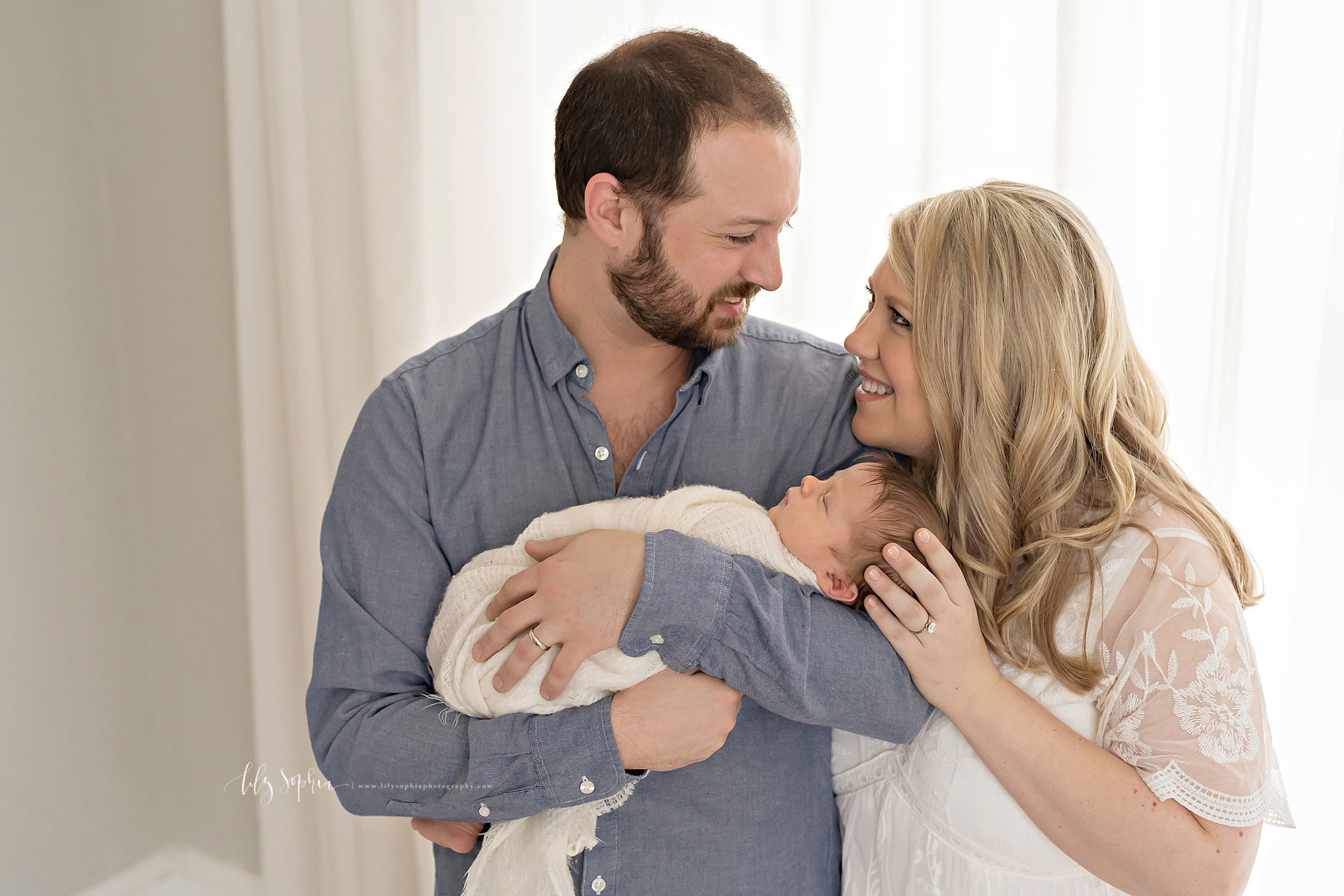 Image of parents of a newborn boy as they stand in a natural light studio.  Dad is wearing a chambray long sleeved shirt and mom is wearing a cream dress.  The husband and wife are smiling and looking one another in the eye.  Dad is cradling his sleeping newborn son in his arms while mom is holding the newborn's head with her left hand.