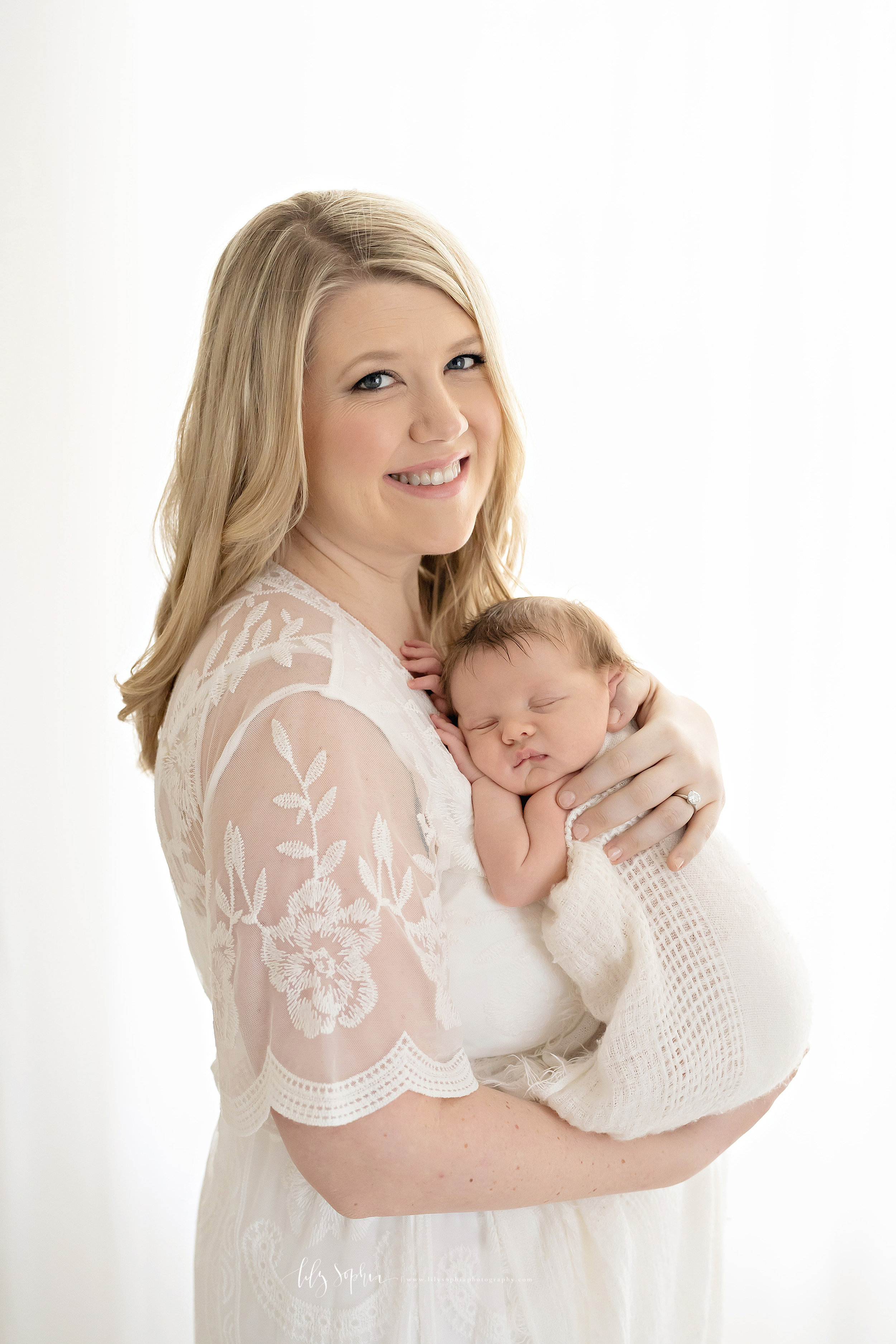 Image of a mom holding her newborn son while standing in a studio in Atlanta. She is smiling as she looks over her right shoulder with her blonde hair flowing behind her. The sleeping  infant is lying against her chest with his hands under his head. Mom has her left hand on the infant's back and her right hand under his bottom.