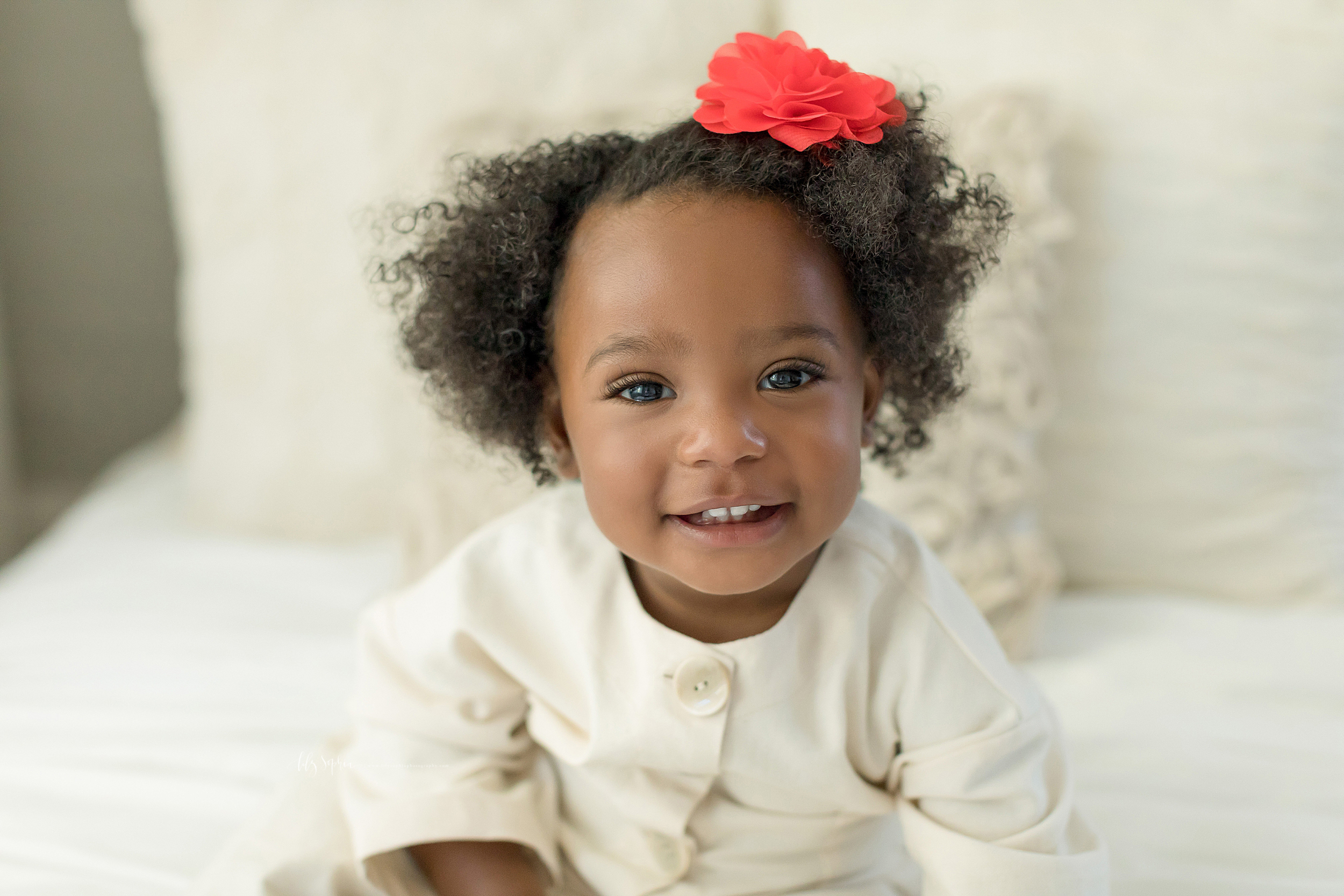 An African American toddler smiles while sitting on a bed for a family photographer in Atlanta.