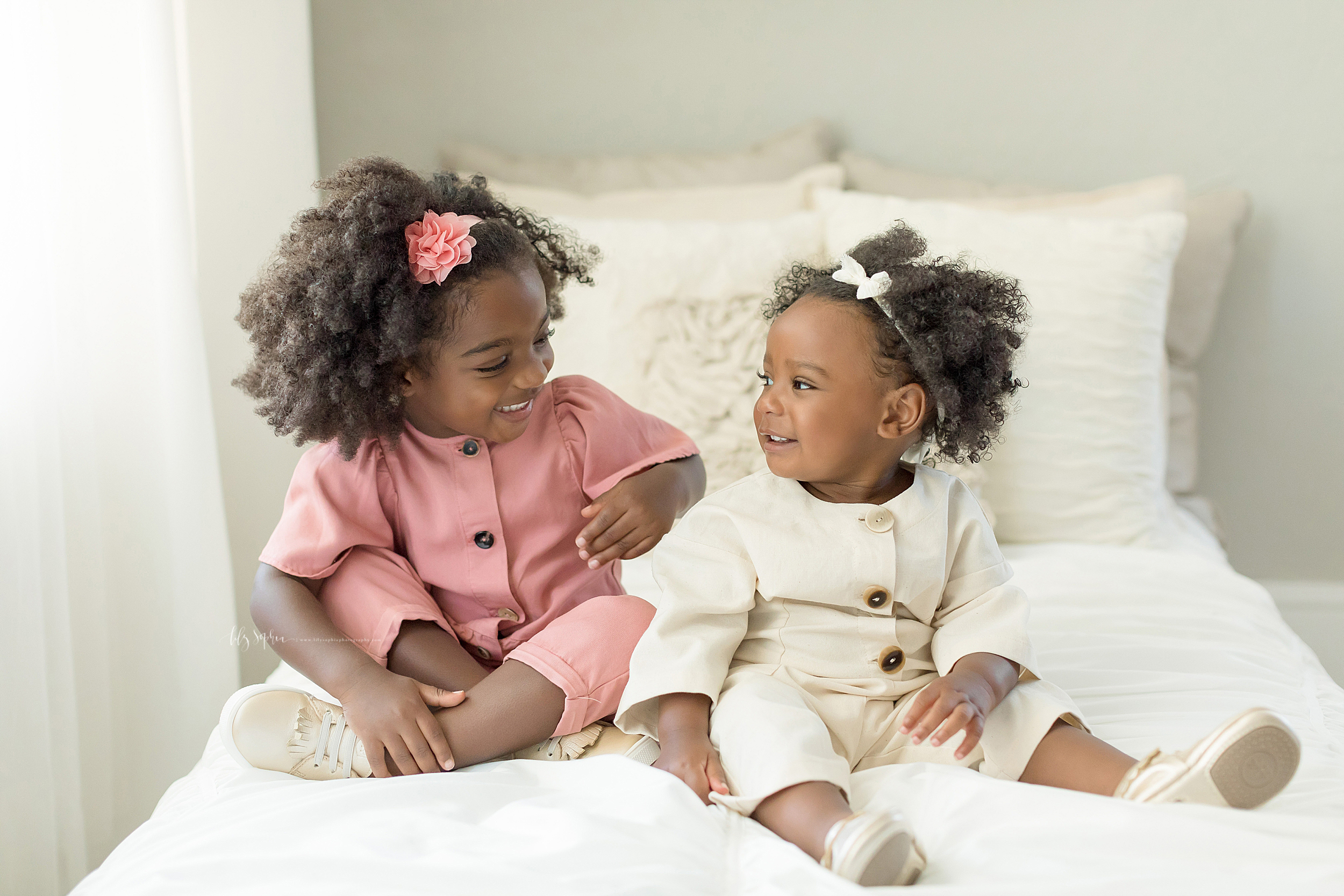 Photograph African American sisters sitting on a bed in an Atlanta studio.  The older sister sports a short sleeved, buttoned down, pink jumpsuit and off- white laced keds. In her hair is a pink rose that holds back her curly black hair. She is smiling at her younger sister who is wearing a long sleeved, buttoned down cream jumpsuit with a bow headband in her hair.