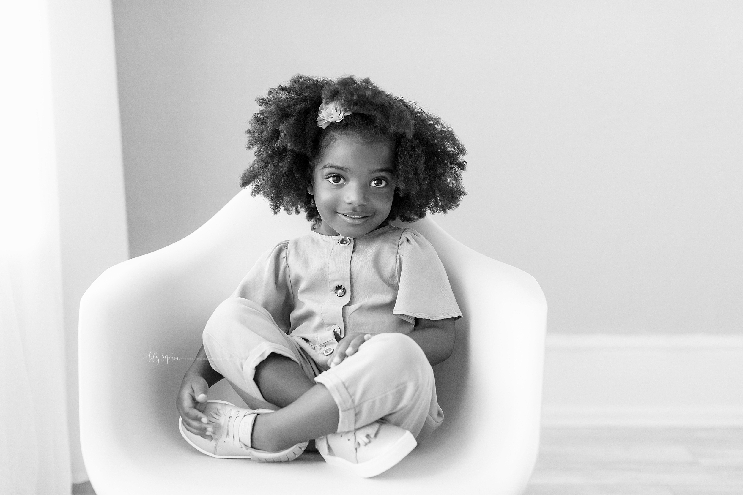 An African American girl sits cross-legged in a modern white chair.