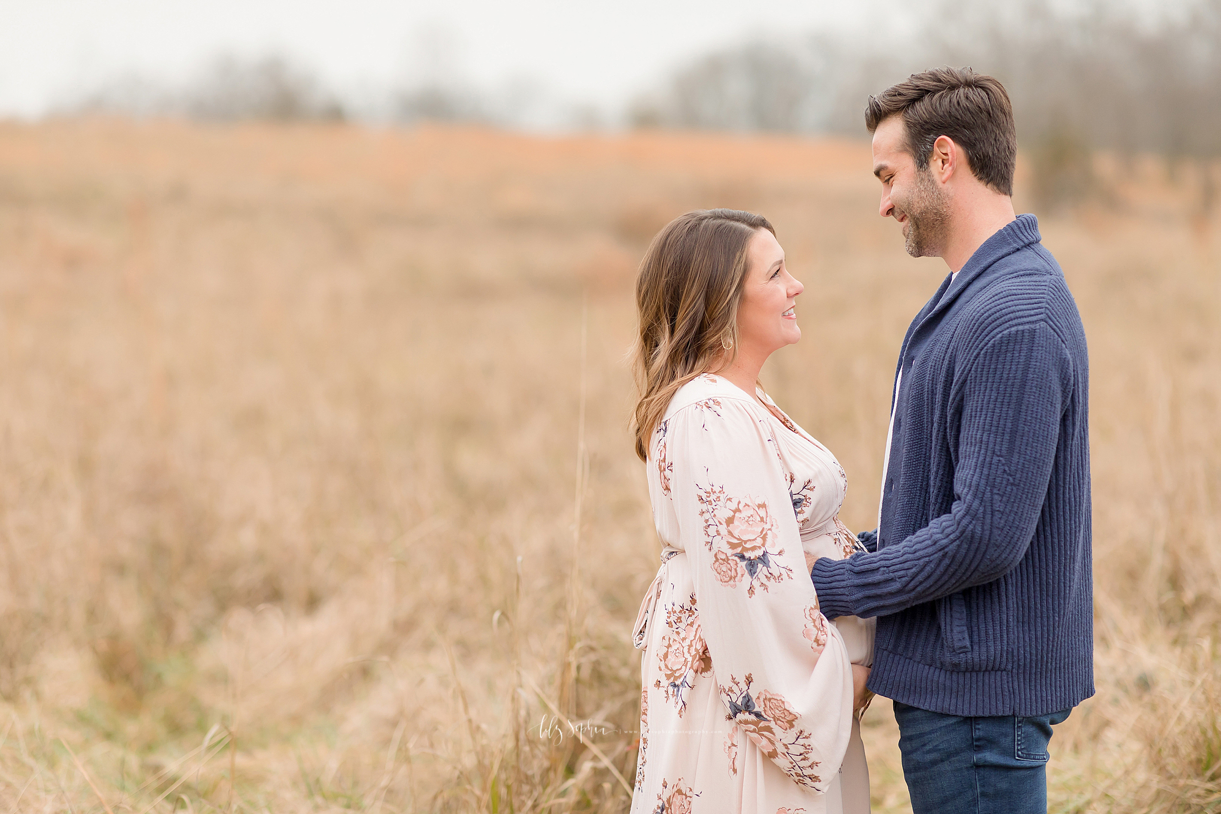 An image of an expectant couple in a field in Atlanta.  The husband wears a blue buttoned down cable knit sweater and blue jeans.  The wife wears a flowered, long-sleeved , empire waist long gown.  The husband caresses his wife's face and holds her at her waist while the look lovingly into each other's eyes.