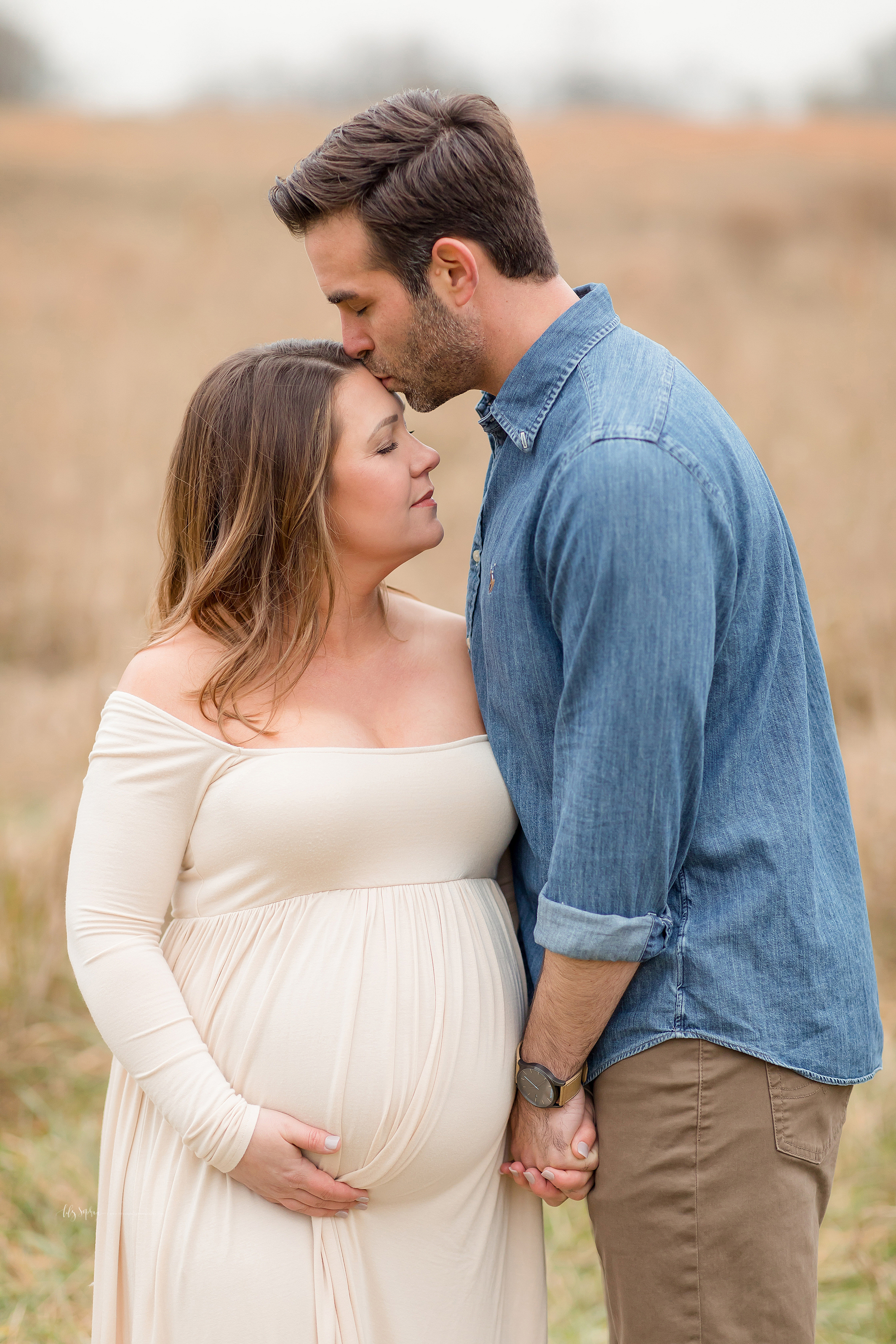 A pregnant wife and her husband are standing in a field in Atlanta.  The husband kisses his wife's forehead as she closes her eyes and holds her pregnant belly in her hand.  The couple holds hands.
