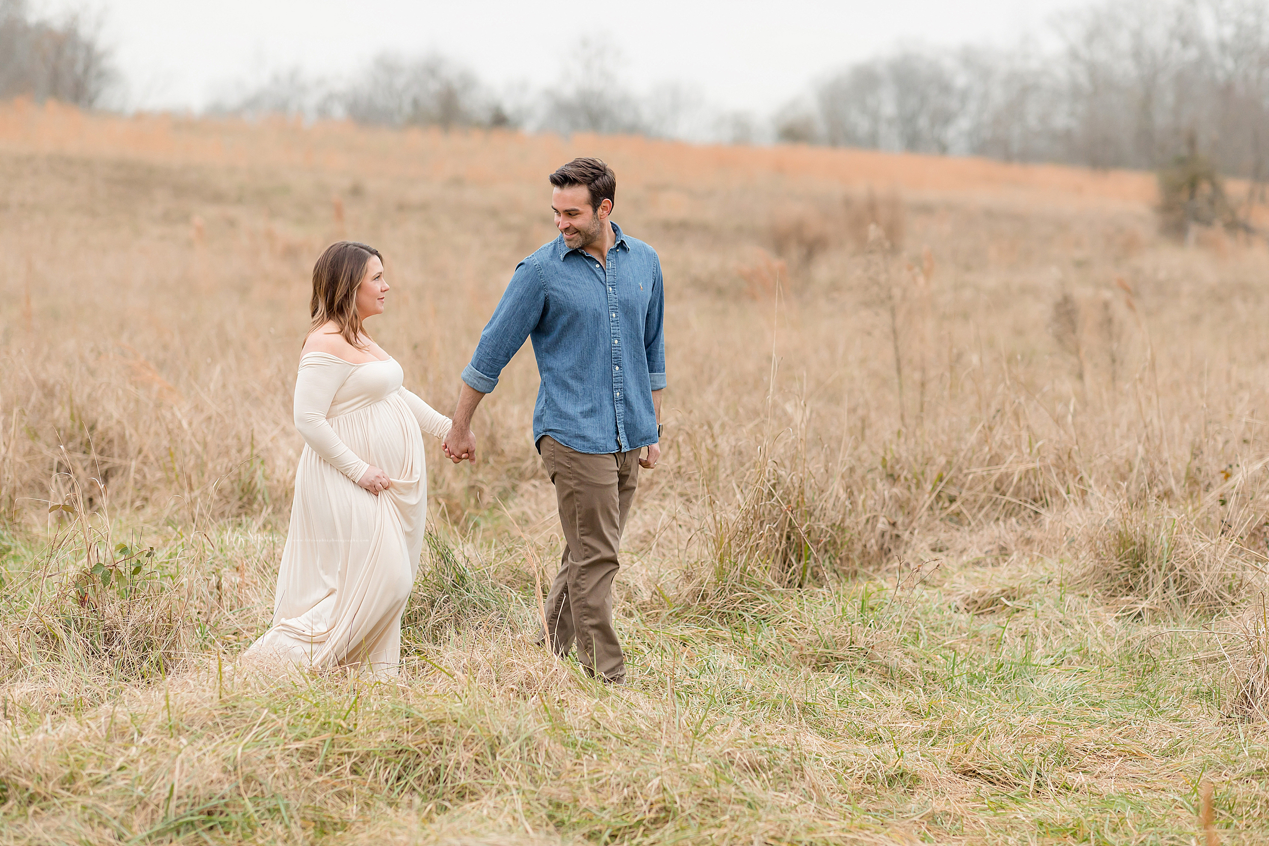 Expectant couple photographing maternity pictures in a field.  The husband leads his pregnant wife hand-in-hand in the field and looks reassuringly at her to express his love for her.