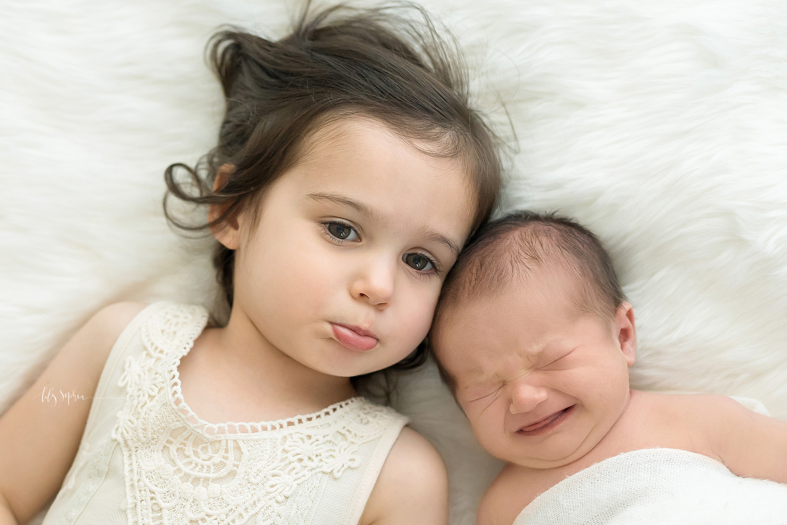 Siblings are lying next to each other on a soft white blanket.  The infant boy with brown hair is crying.  The toddler girl wearing a sleeveless white lace dress is pouting because she is sad that her brother is not happy.