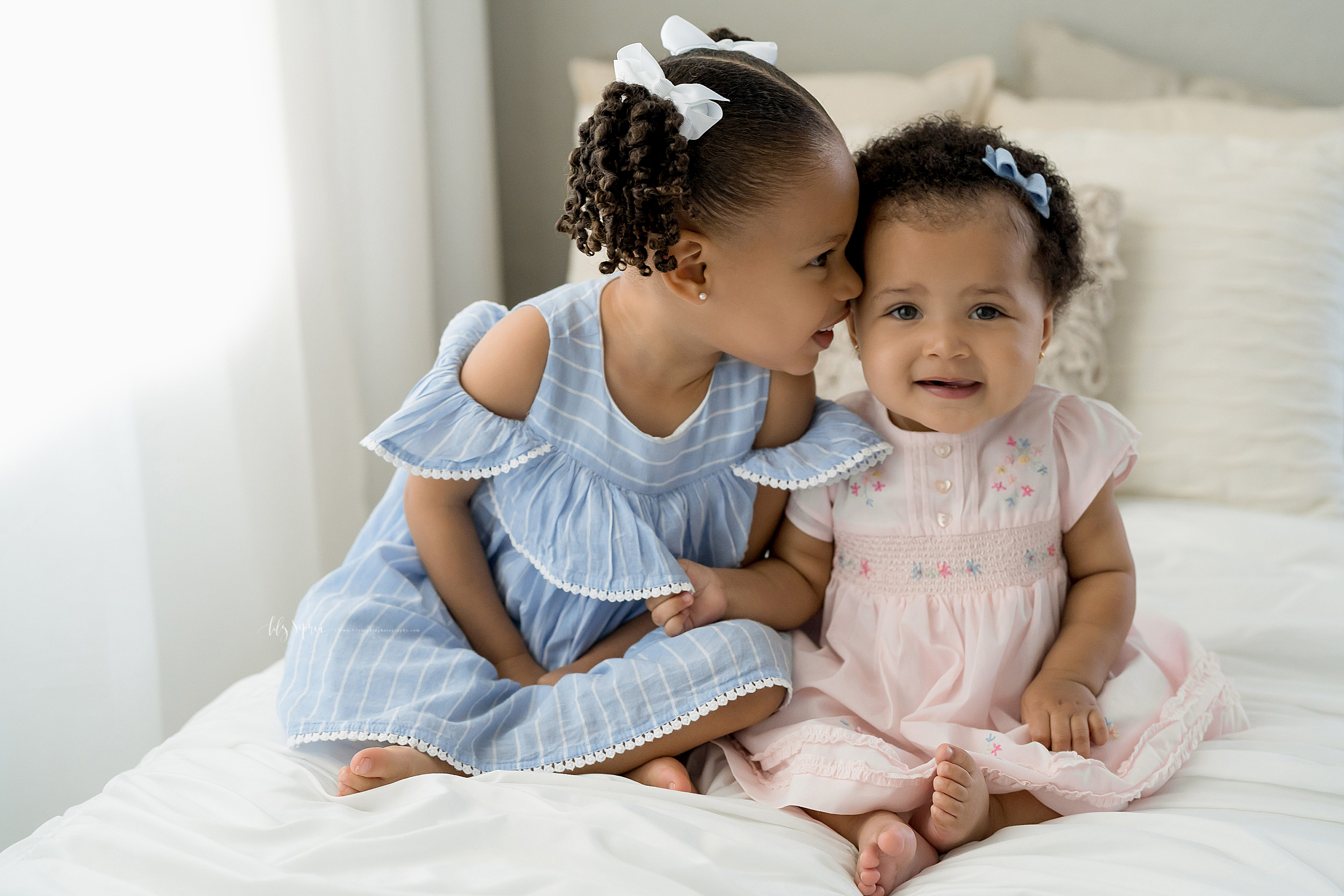 Photograph of two African-American sisters sitting on a bed in front of a window. The older sister is whispering something in her younger sister's ear while the younger sister smiles.  The toddler is wearing a blue and white striped cold shoulder dress and white bows in her hair around her pigtails.  The baby is wearing a delicate pink smocked dress with blue and pink embroidered flowers and translucent buttons down the center and a blue bow on the left side of her head.