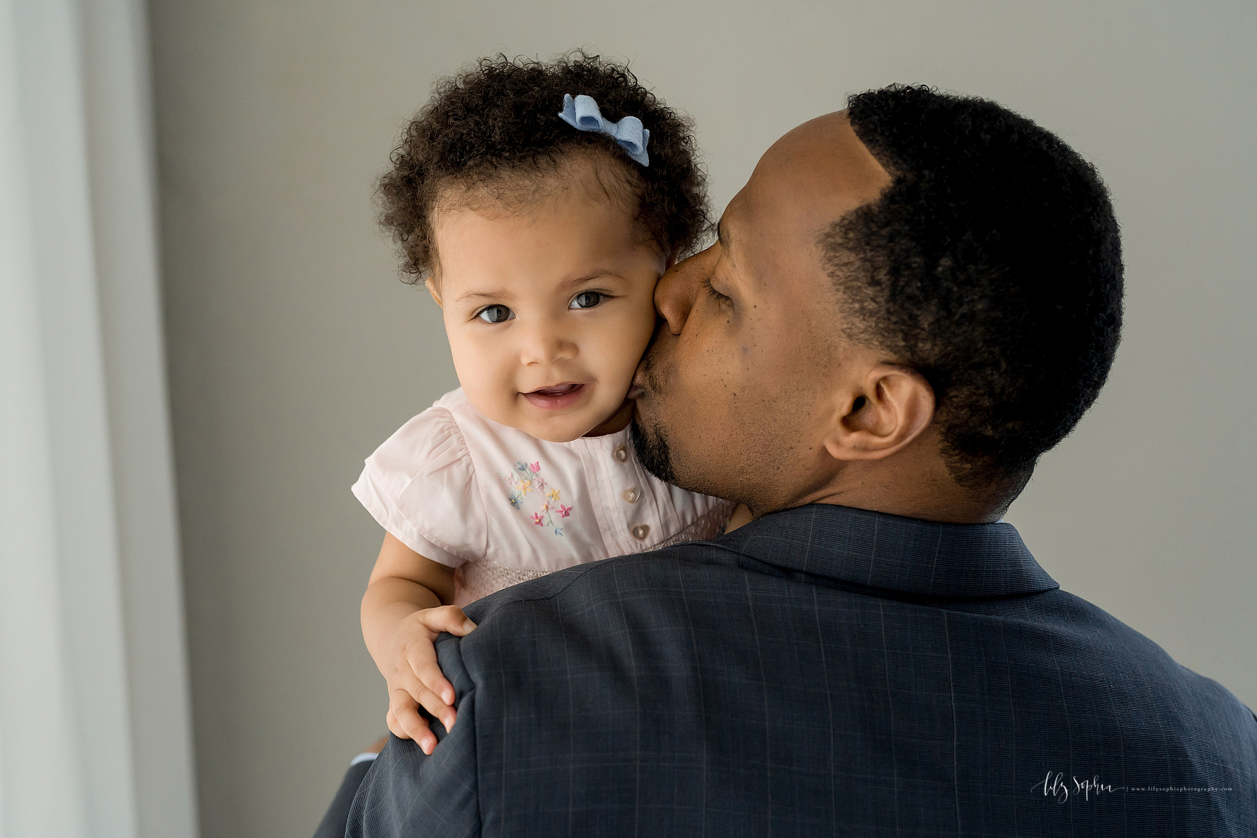 Photograph of an African-American Dad holding his baby daughter.  The baby daughter is looking over the right shoulder of the father as he kisses her cheek.