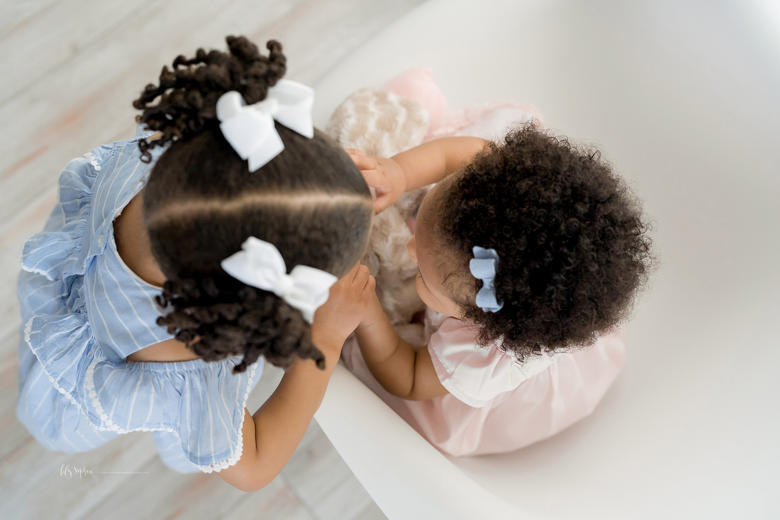 Image of an aerial view of two African-American little girls.  The younger girl is sitting in a modern molded white chair and her sister is standing next to the right side of the chair.  The girls are holding each other's hands.  The image shows the bows in their curly black hair.