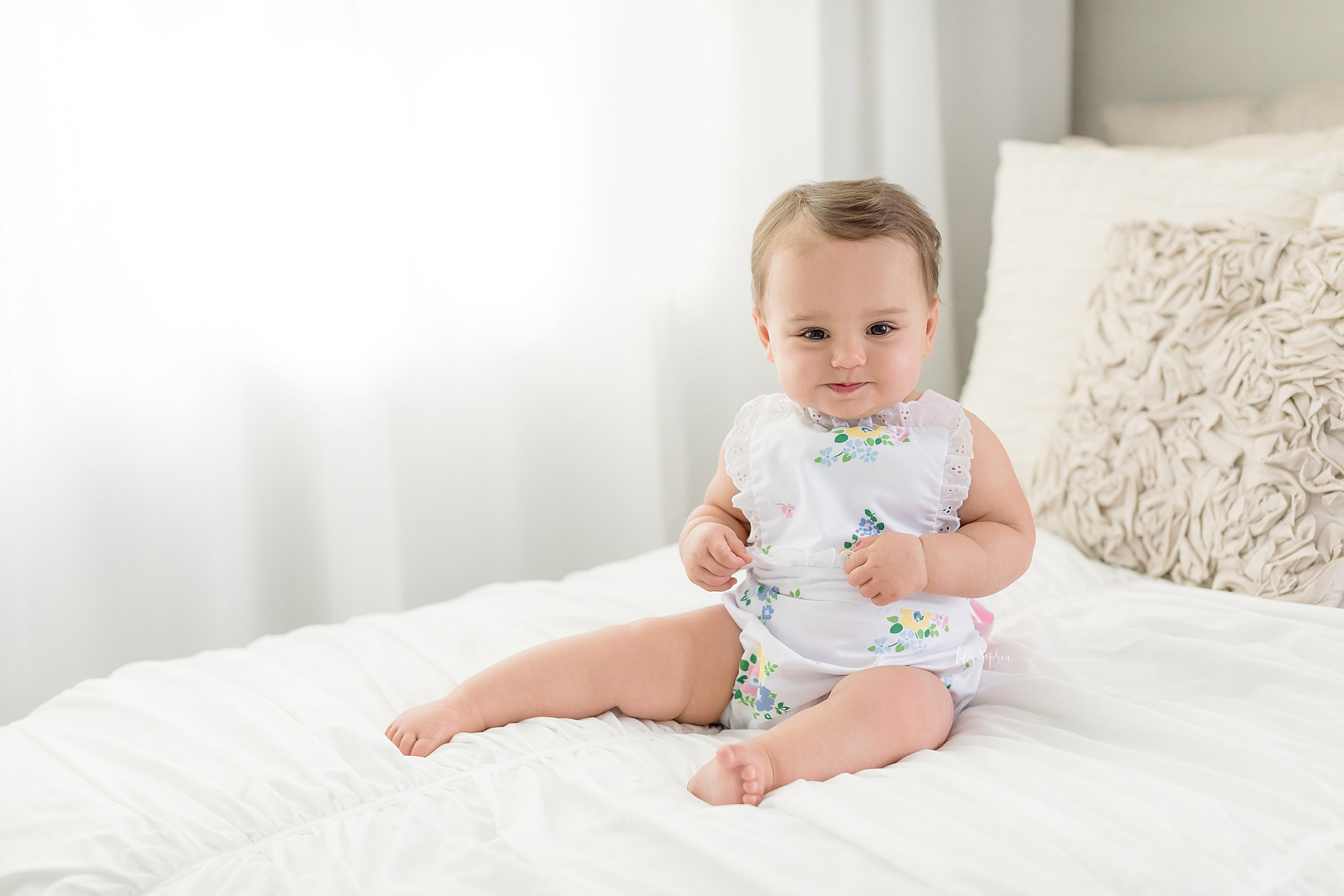 A happy one year old sits on a bed with a white spread and a cream brocade pillow.  She is barefoot and is wearing a white and pastel floral sunsuit.  She has brown hair and brown eyes.