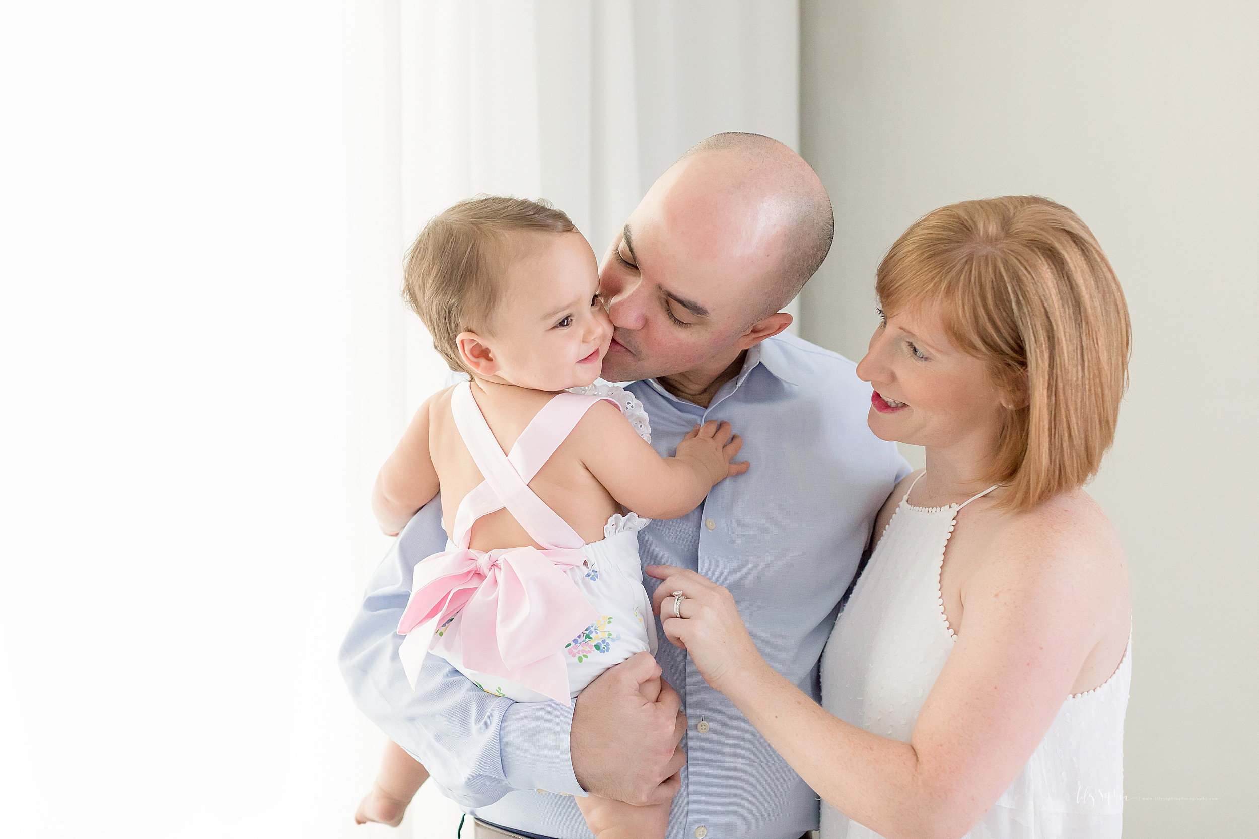 Mom, Dad and one year old in a natural light studio in Atlanta pose for a picture.  Balding Dad is hold his daughter and kissing her on the cheek.  Red haired mom is looking at the daughter and reaching out to tickle her.  The one year old is smiling and holding on to Dad's arm and chest.