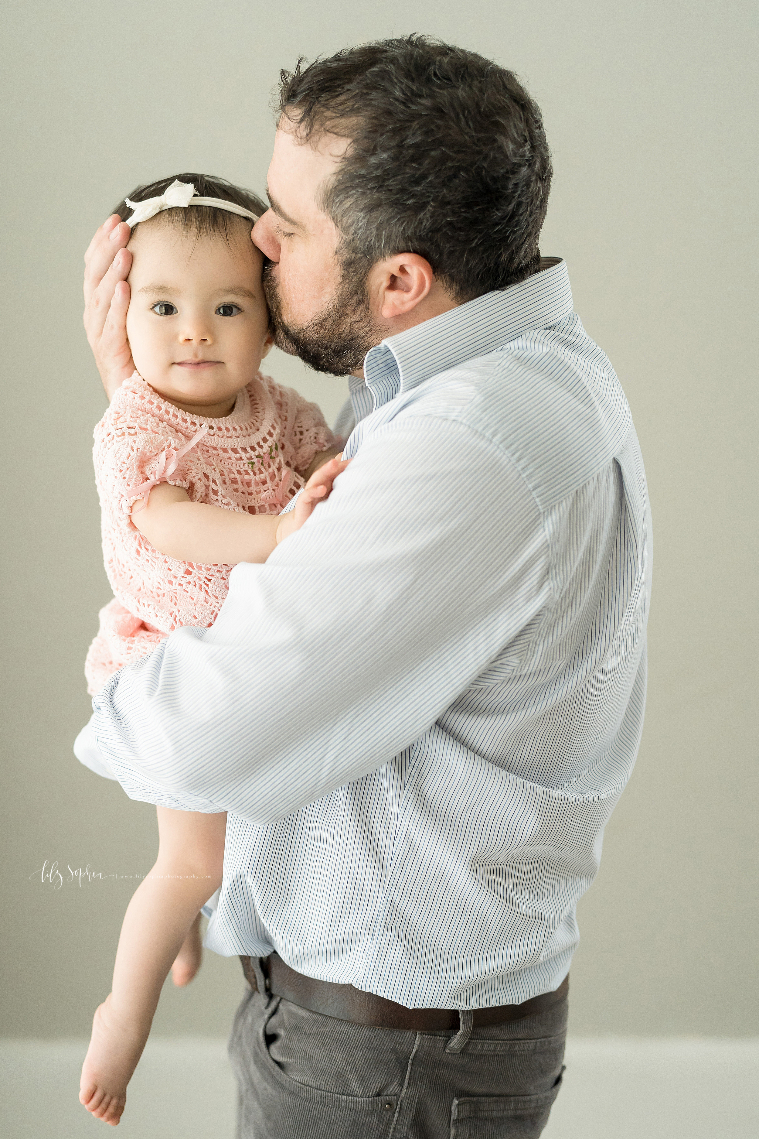 Photograph of bearded dad holding his one year old daughter while he is standing. Dad is wearing gray jeans with a black belt and a white and gray long-sleeved pin-striped shirt.  His daughter is wearing a pastel pink bowed headband in her hair and a pastel pink crocheted dress. Dad's right hand is cradling his daughter's head as he kisses her head.  Dad's left hand holds his daughter as her tender legs and barefoot feet dangle.