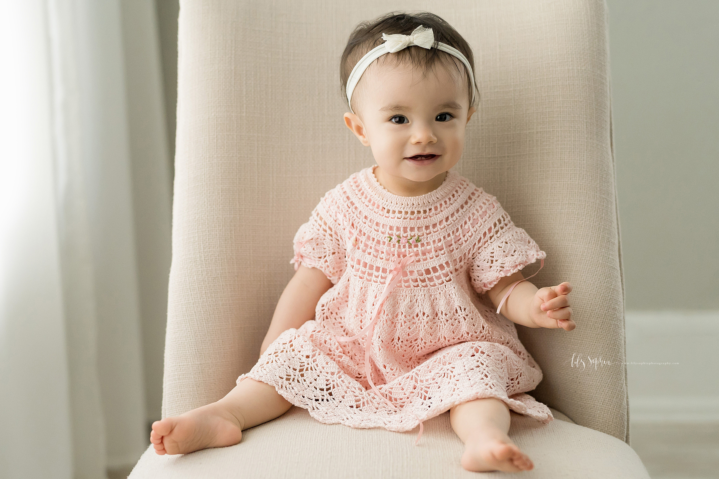 Photograph of an Asian one year old sitting on a cream linen armless chair in front of a window with sheer panel drapes. She is barefoot with her legs spread apart and is wearing a pastel pink crocheted dress with three delicate roses sewn on the front and a delicate pink ribbon bow.  The short sleeves have pink ribbon bows woven through the crocheted fabric at the bottom.  Her arm is bent at the elbow and she is gesturing with her left hand.  Her right arm is at her side.