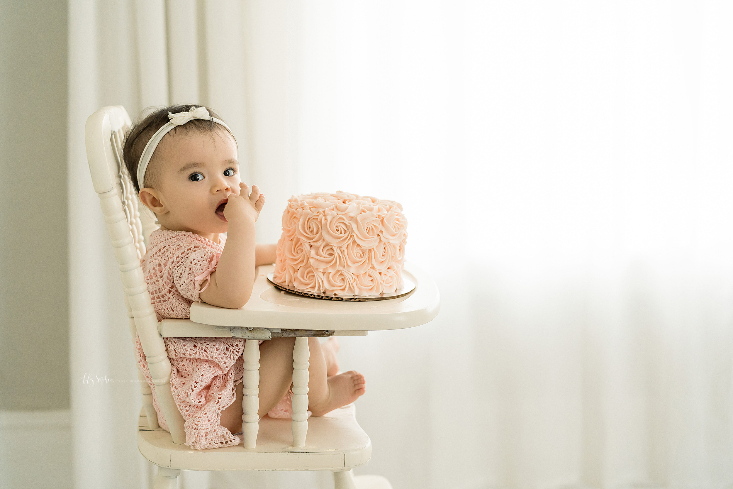 Image of an Asian one year old girl  in a cream wooden high chair.  The little girl is wearing a pastel pink headband with the bow and a crocheted dress.  She has her right hand in her mouth tasting the frosting of the pink rose covered smash cake.  The smash cake sits on the tray of the high chair.