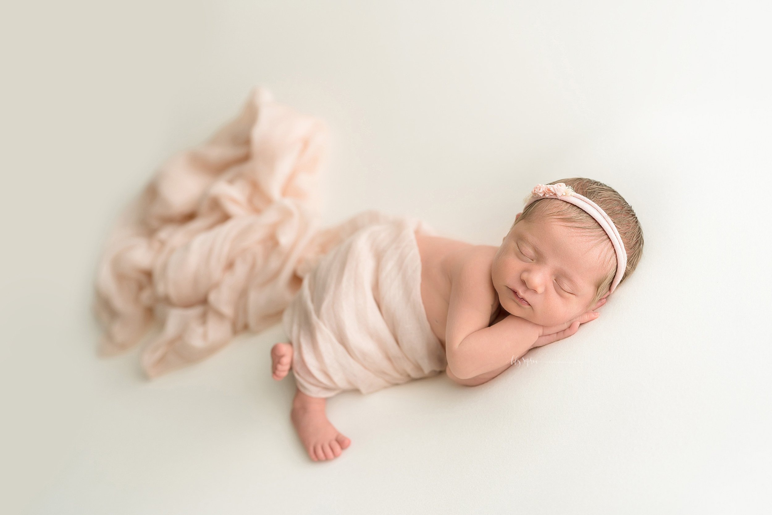 Newborn baby girl sleeping with her hands under the left side of her face. She is wrapped in a pastel pink linen swaddle and is wearing a pastel pink headband with a delicate bow on top of her head.  Her tiny feet are sticking out of the swaddle.
