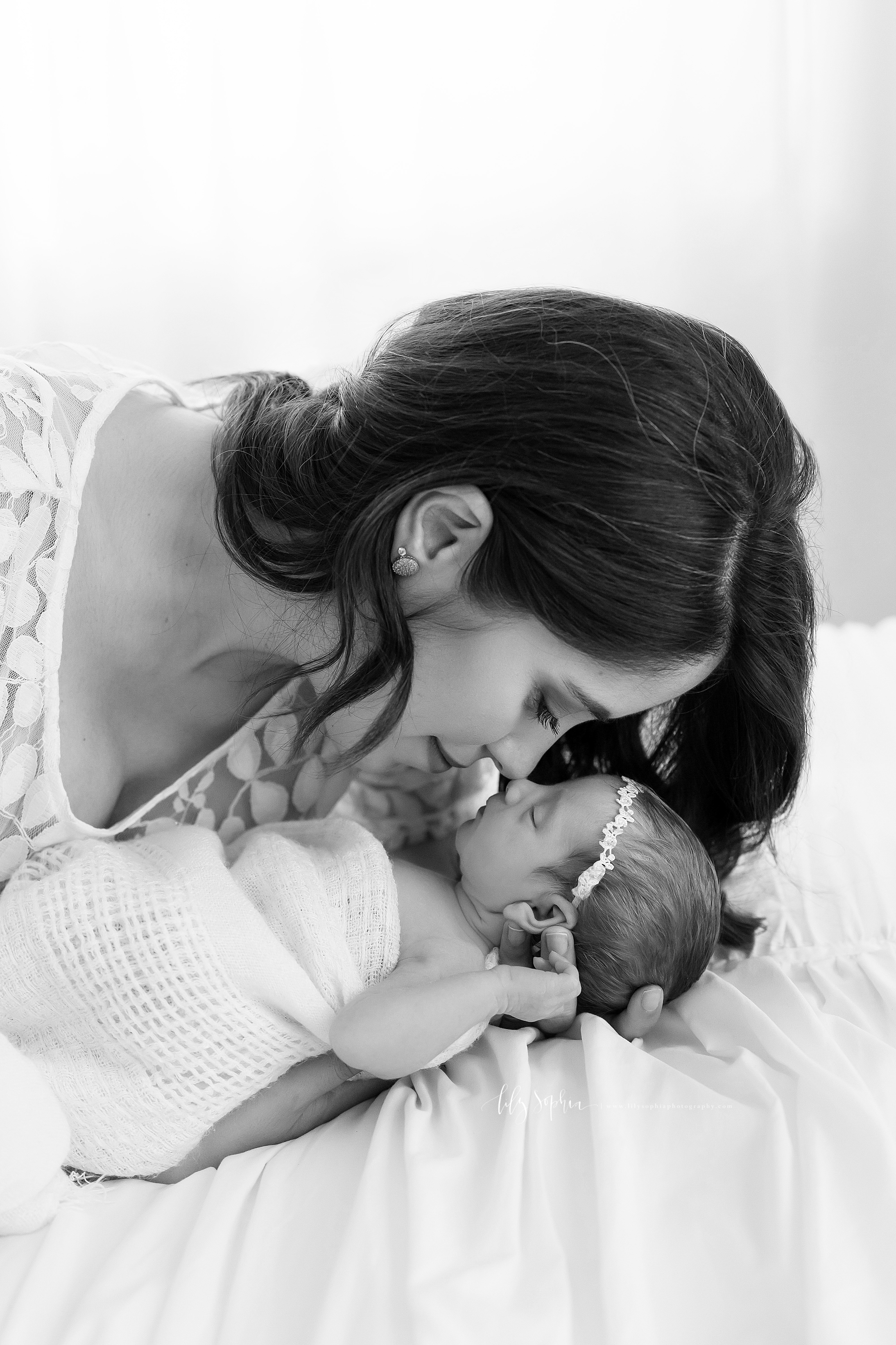 A black and white image of a mom and her newborn daughter nose to nose lying on a bed.  The brunette mom is wearing a shear lace bodiced scooped-necked dress.  Her daughter is wearing a lace headband and is loosely wrapped in a swaddle blanket.  The daughter is sleeping as mom cradles her head in her left hand.