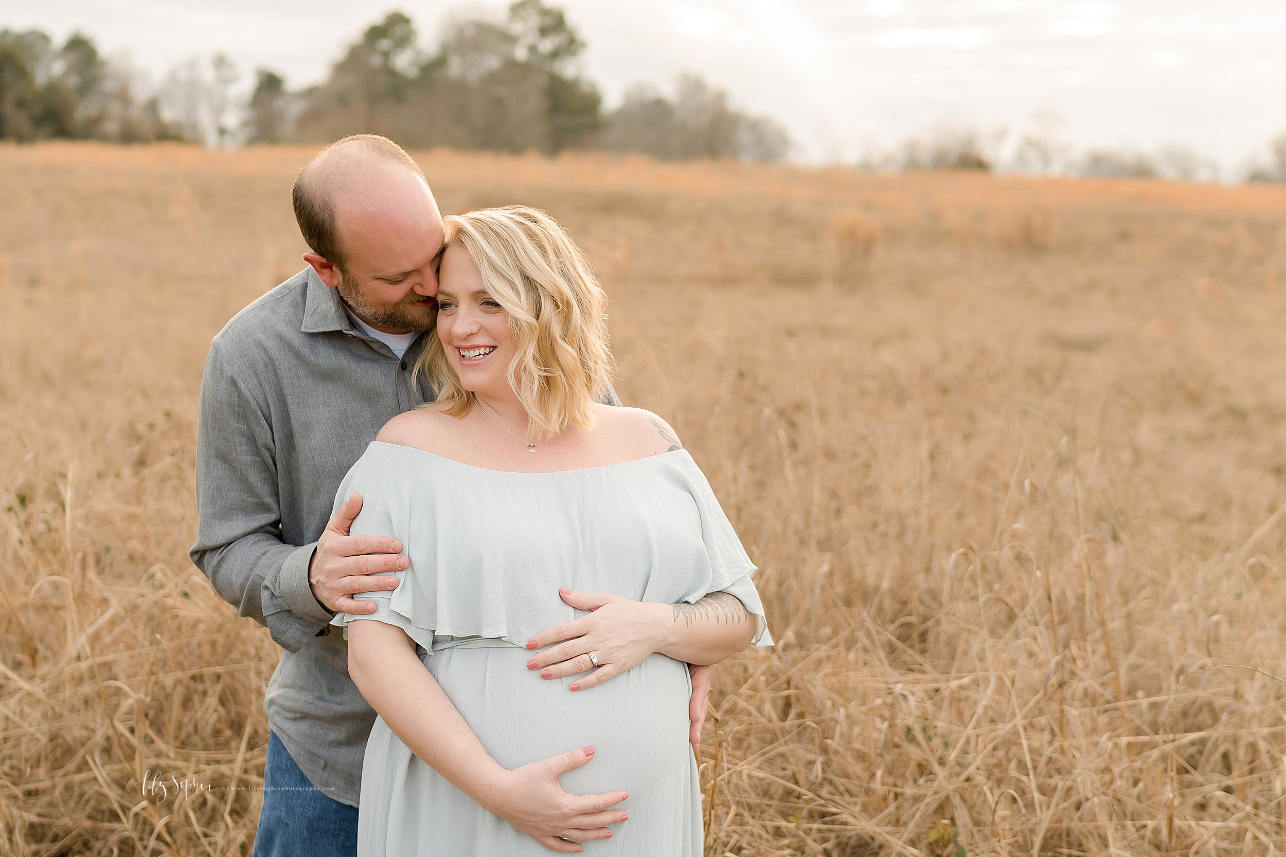 Maternity photograph of a husband and wife in a field at sunset. The bearded husband is standing behind his wife in a gray long-sleeve button down shirt and blue jeans. He has his right hand on her right upper arm and he is whispering in her ear. The blonde wife has her back to her husband and is looking over her right shoulder while holding her pregnant belly with her right arm below her belly and her left arm above her belly. She is wearing an off the shoulder short sleeve pale blue full-length flowing maternity dress and she is smiling at what her husband told her. At the neckline is a large flowing ruffle and at the empire waist is a thin fabric tie.