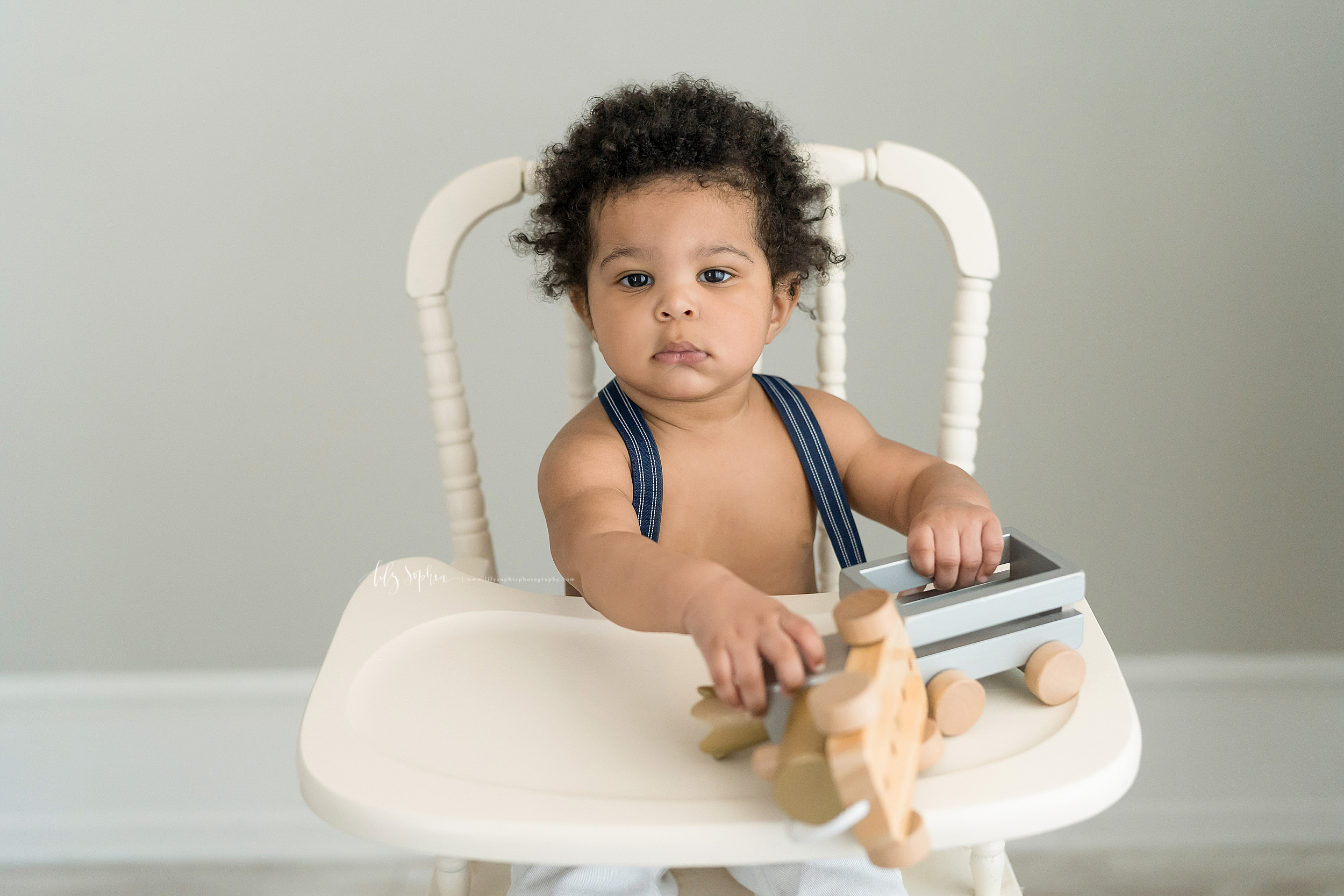 Photograph of an African-American boy with short curly brown hair and bright brown eyes sitting in a cream colored antique high chair. He is bare chested and is wearing blue and white striped suspenders. He has a wooden toy truck that is pulling a pastel blue open flatbed on the tray of the high chair.