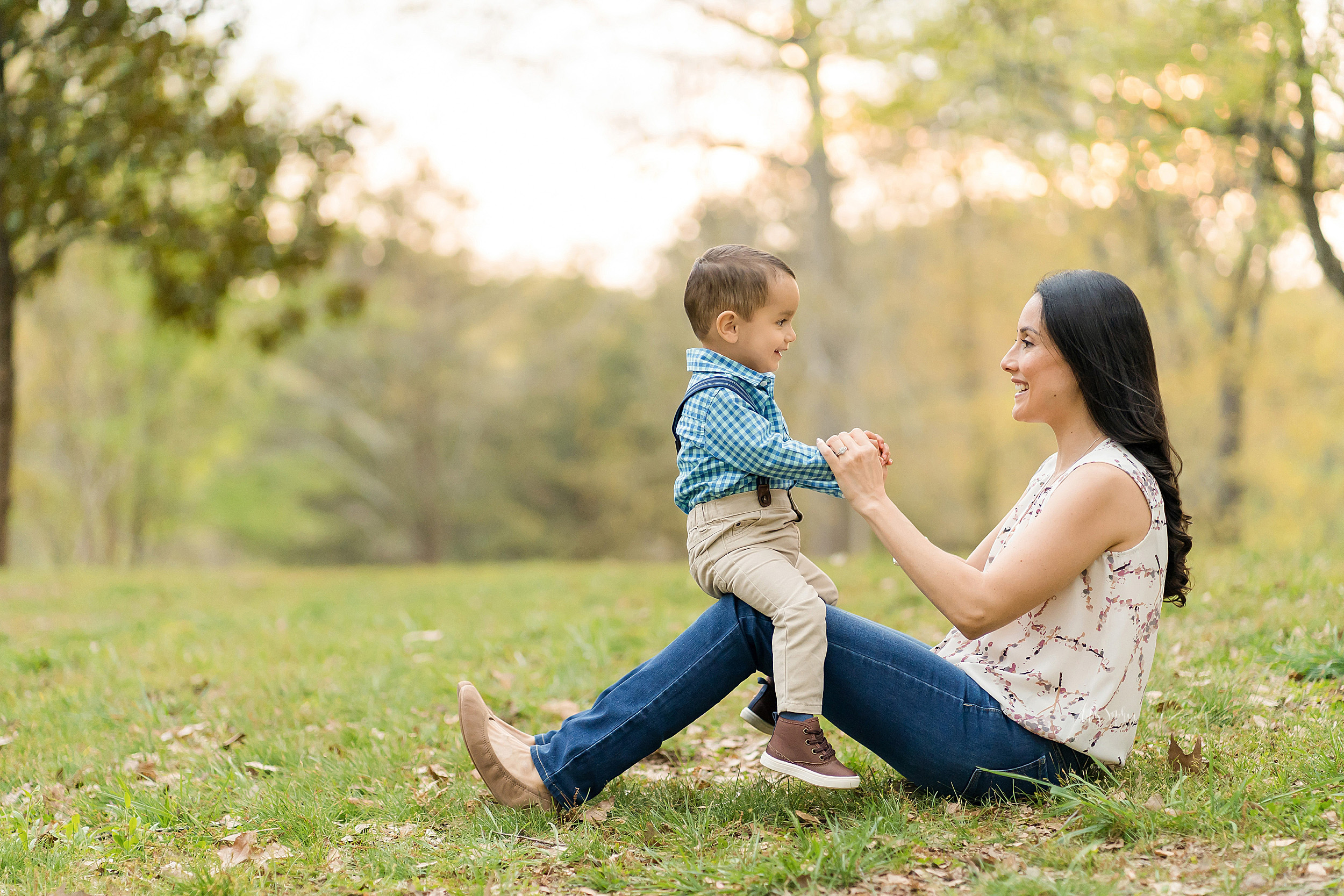 Profile image of a happy two year old caucasian boy and his mom smiling at one another in a park at sunset. Mom is sitting on the grass with her knees bent. Her two year old son is straddling her knees and holding her hands.
