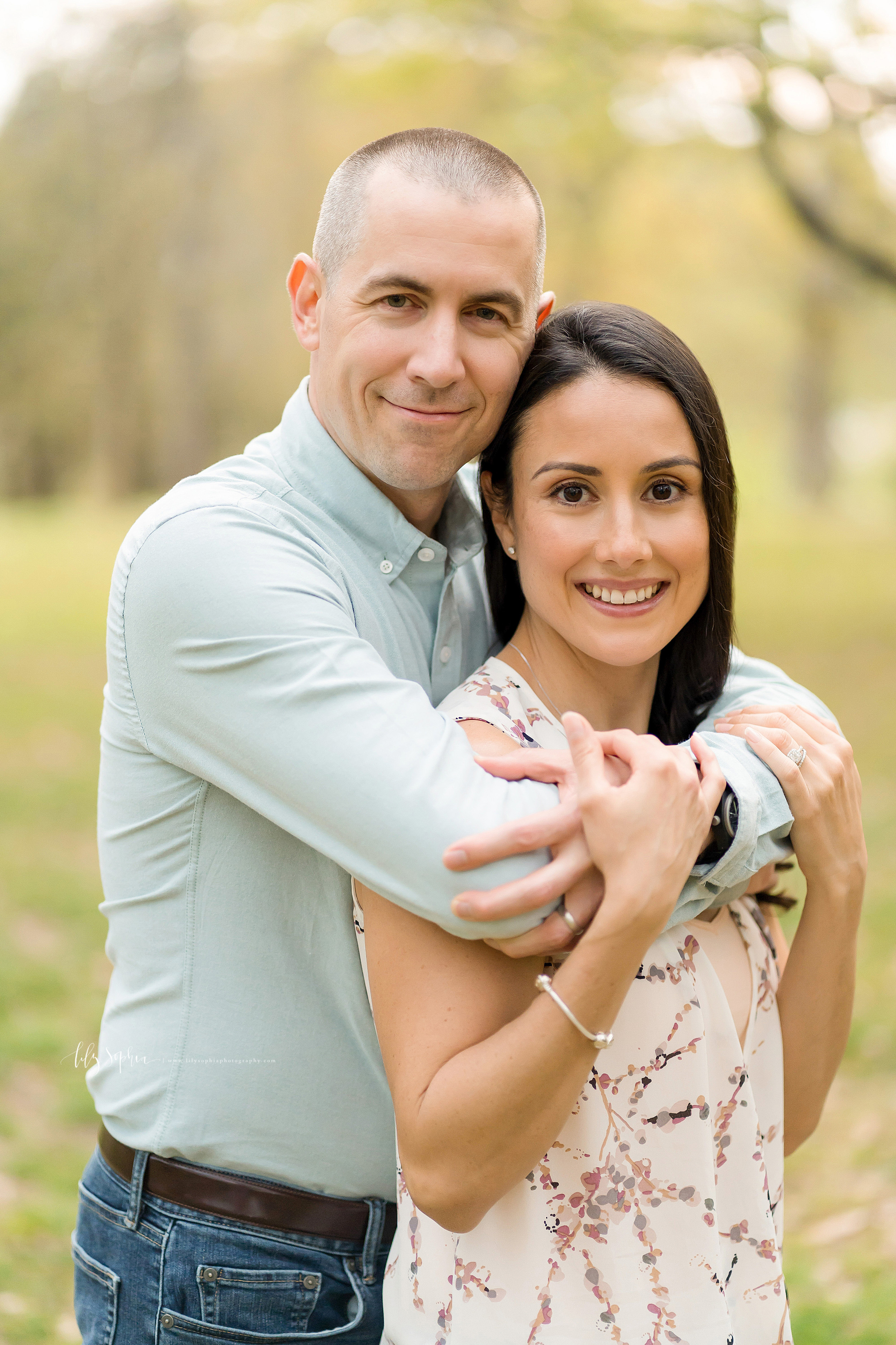 Image of a smiling husband and wife in a park in Atlanta at sunset.  Dad is standing behind his wife with his hands wrapped around her shoulders.  Mom is holding Dad's arms.