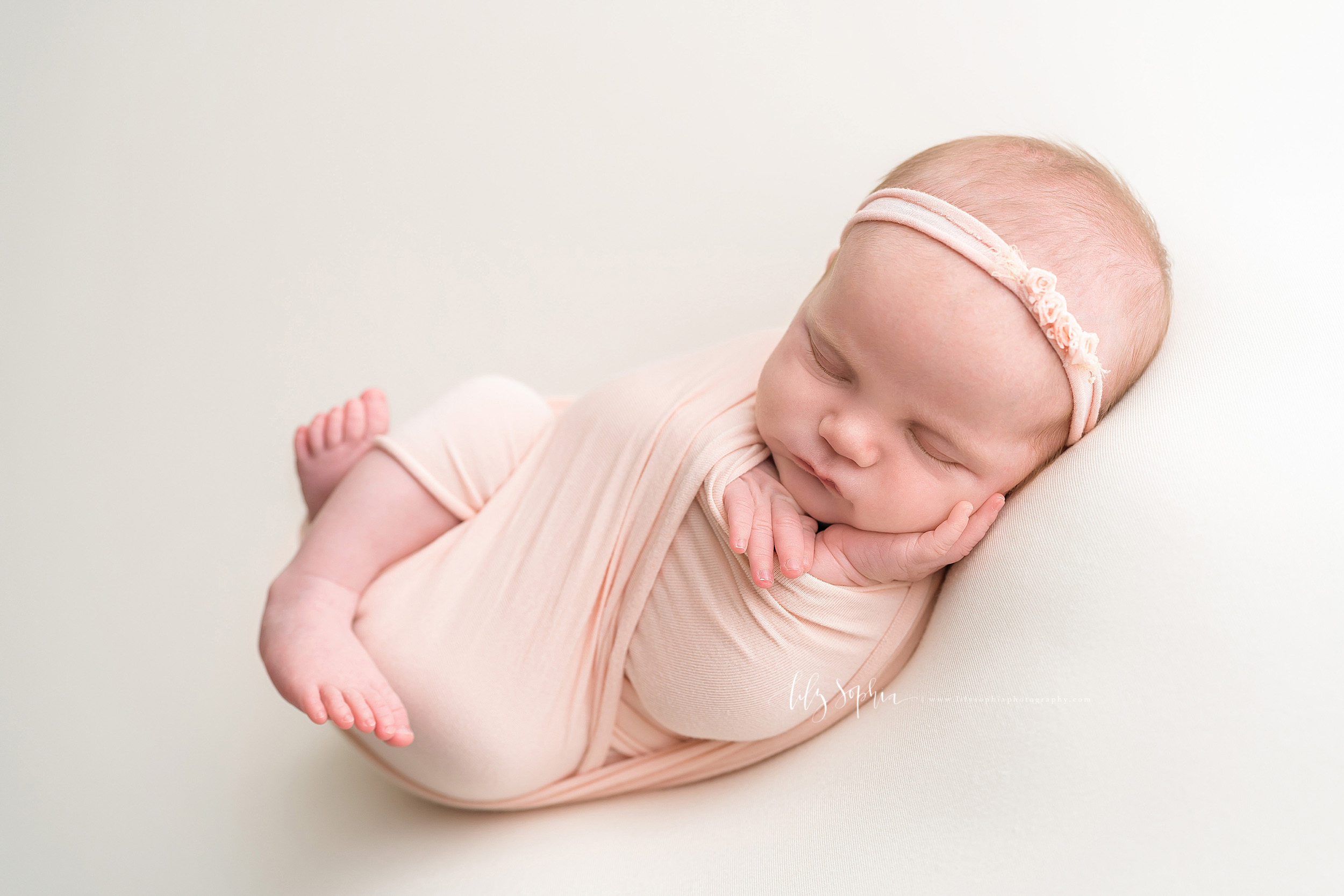 Image of a sleeping infant girl wrapped in a knit pale pink swaddle.  Her legs are bent and her feet are sticking out the bottom of the swaddle while her little hands are sticking out the top.  Her left hand is open and resting on her cheek.  She is wearing a pale pink headband with three tiny roses.