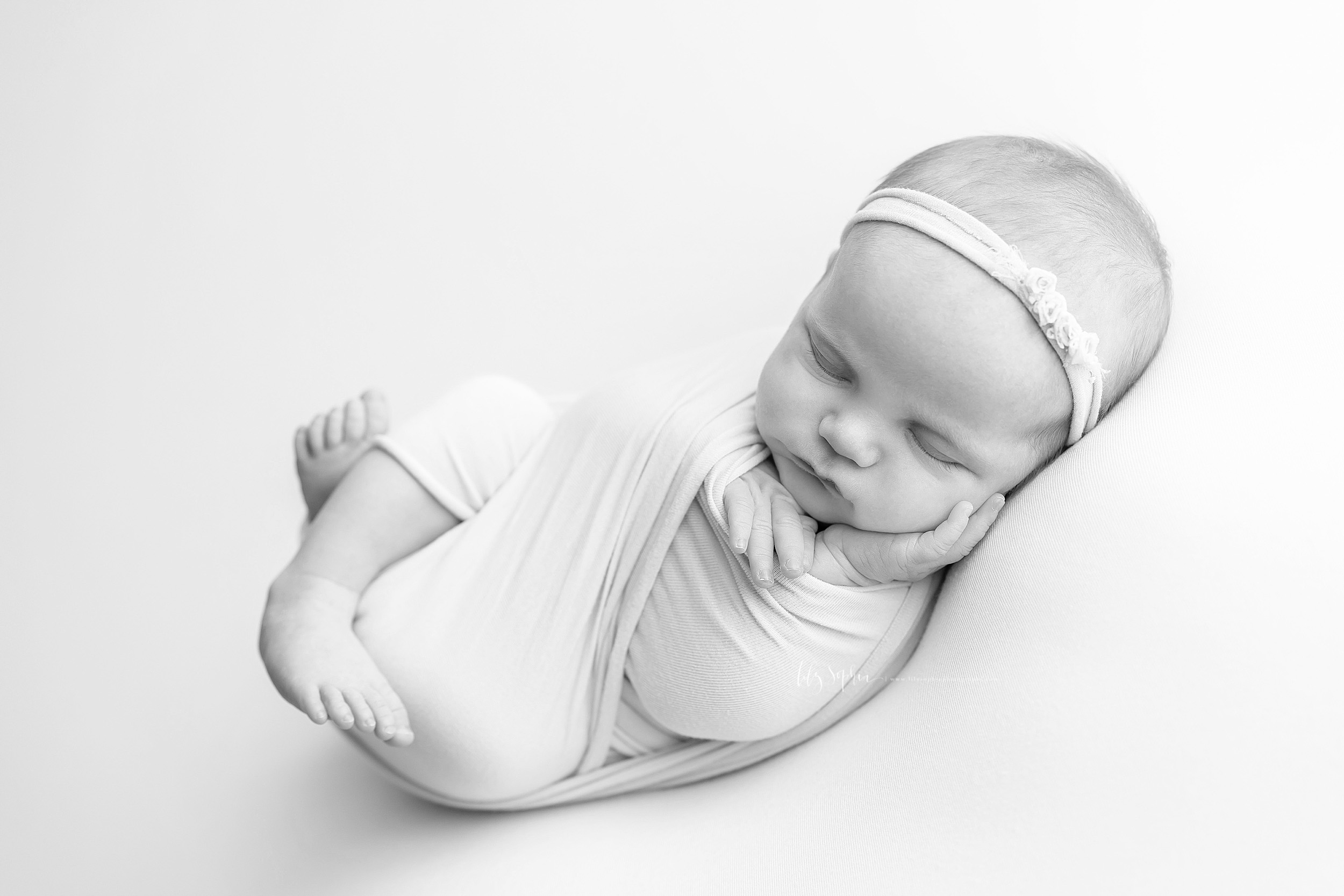 Black and white image of a sleeping infant girl wrapped in a knit  swaddle. Her legs are bent and her feet are sticking out the bottom of the swaddle while her little hands are sticking out the top. Her left hand is open and resting on her cheek. She is wearing an elastic headband with three tiny roses on it in her hair.