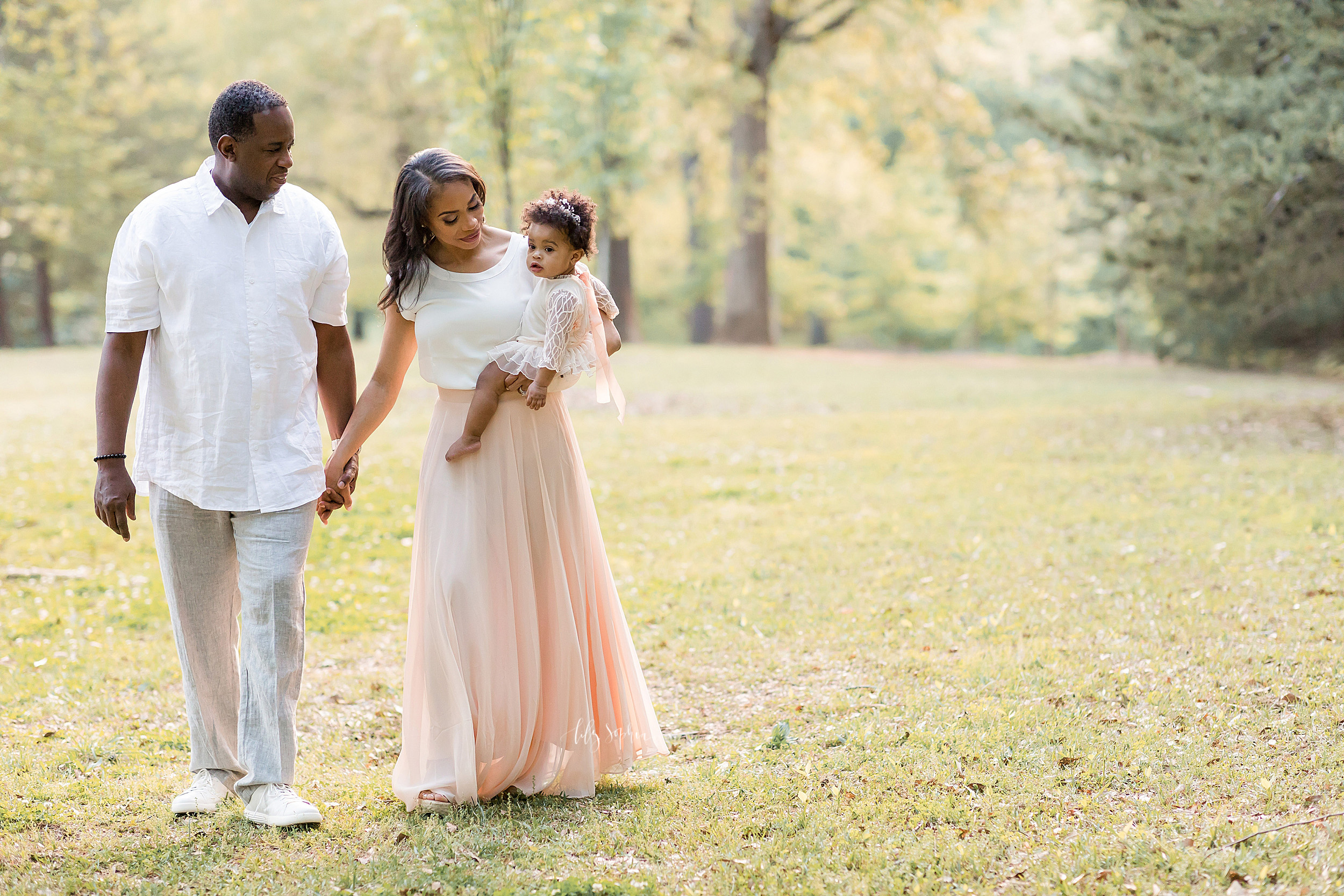 Family photo of three as they walk in an Atlanta park at sunset celebrating their daughter turning one.