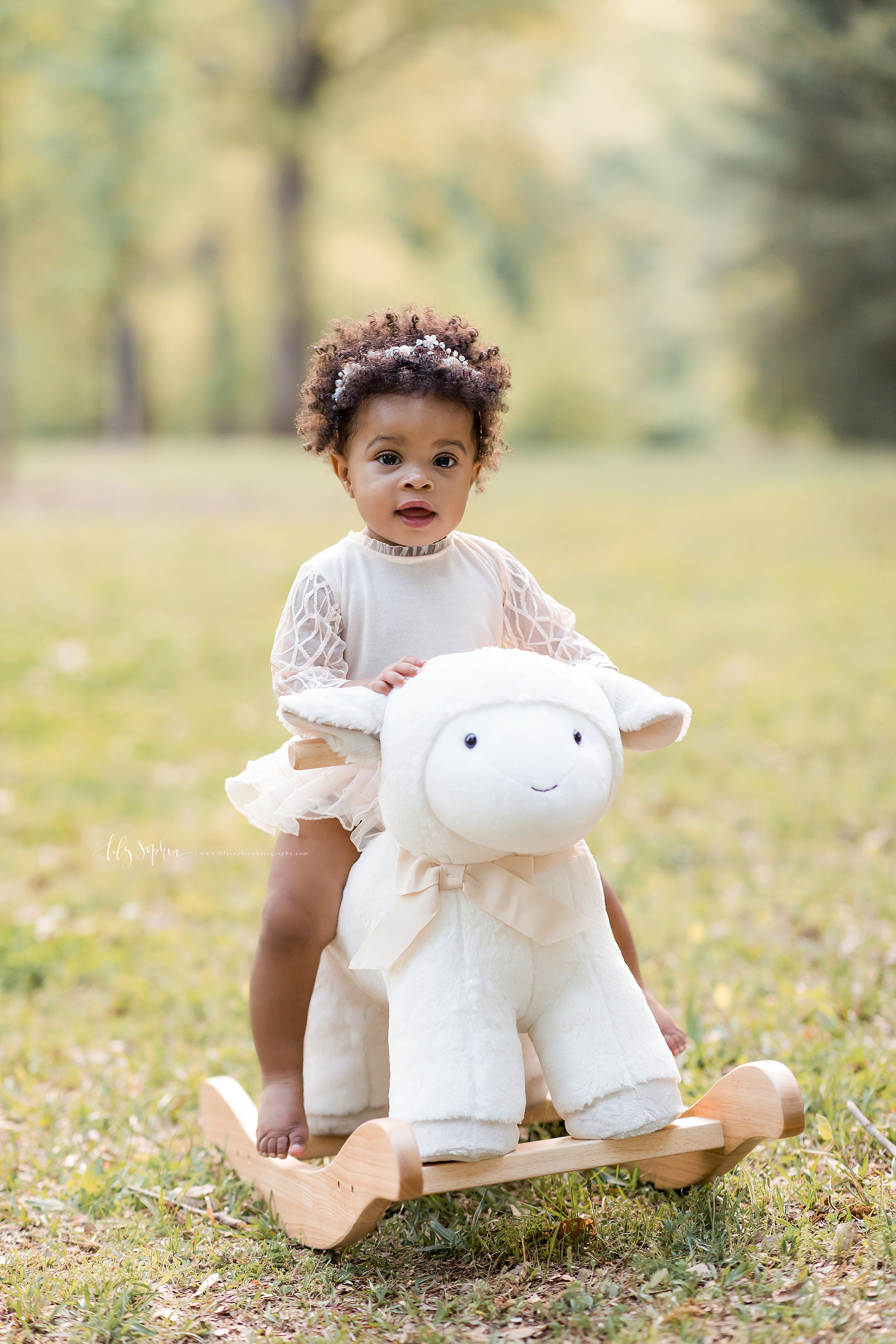 Image of an African-American one year old girl riding a rocking lamb at sunset in an Atlanta park.