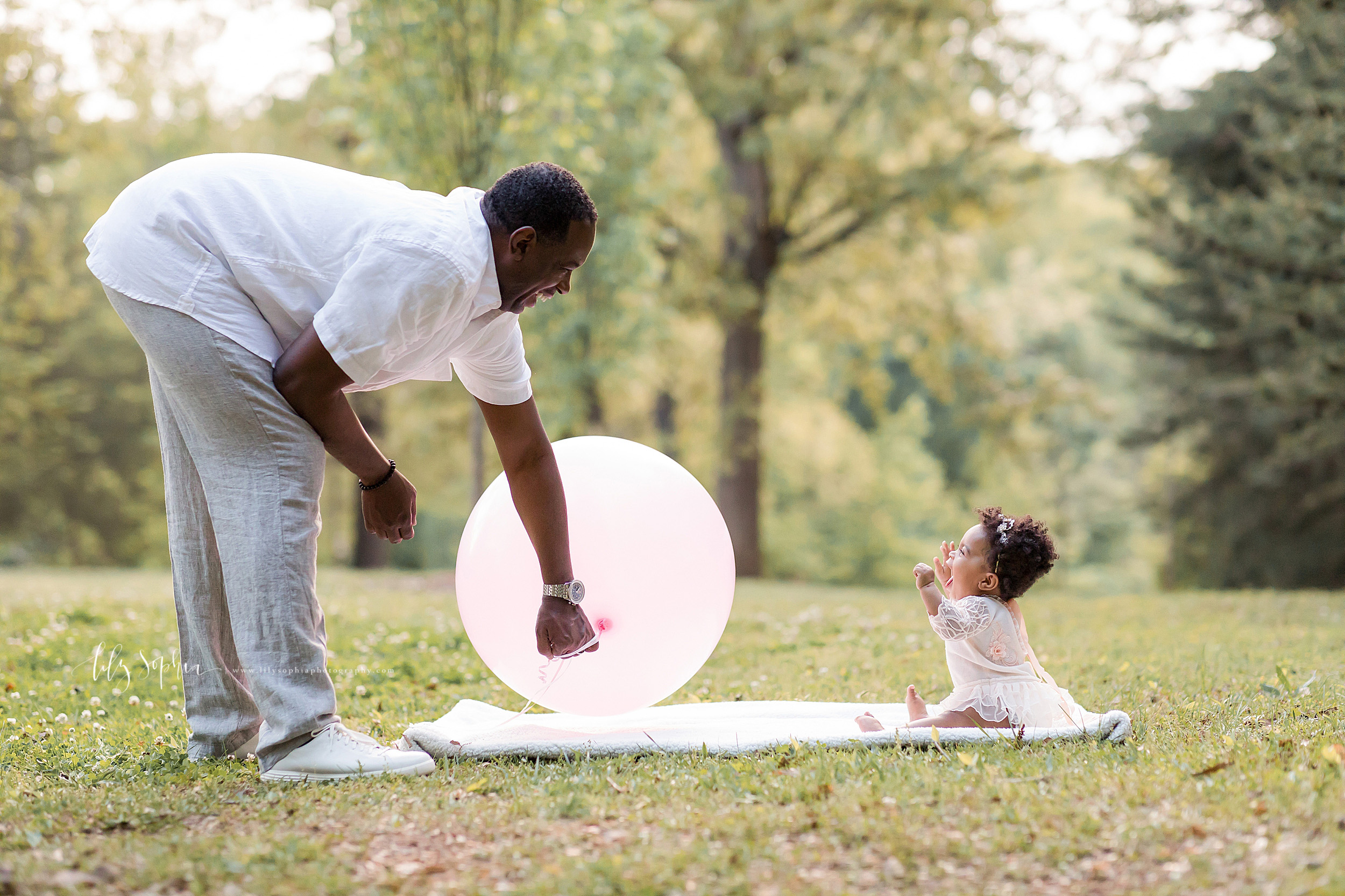 Image of an excited one year old African-American girl in a park with her dad. The little girl is sitting on a blanket at sunset with her arms up in the air and her mouth wide open. Her father is bending over the blanket and holding a large pink balloon for her first birthday.