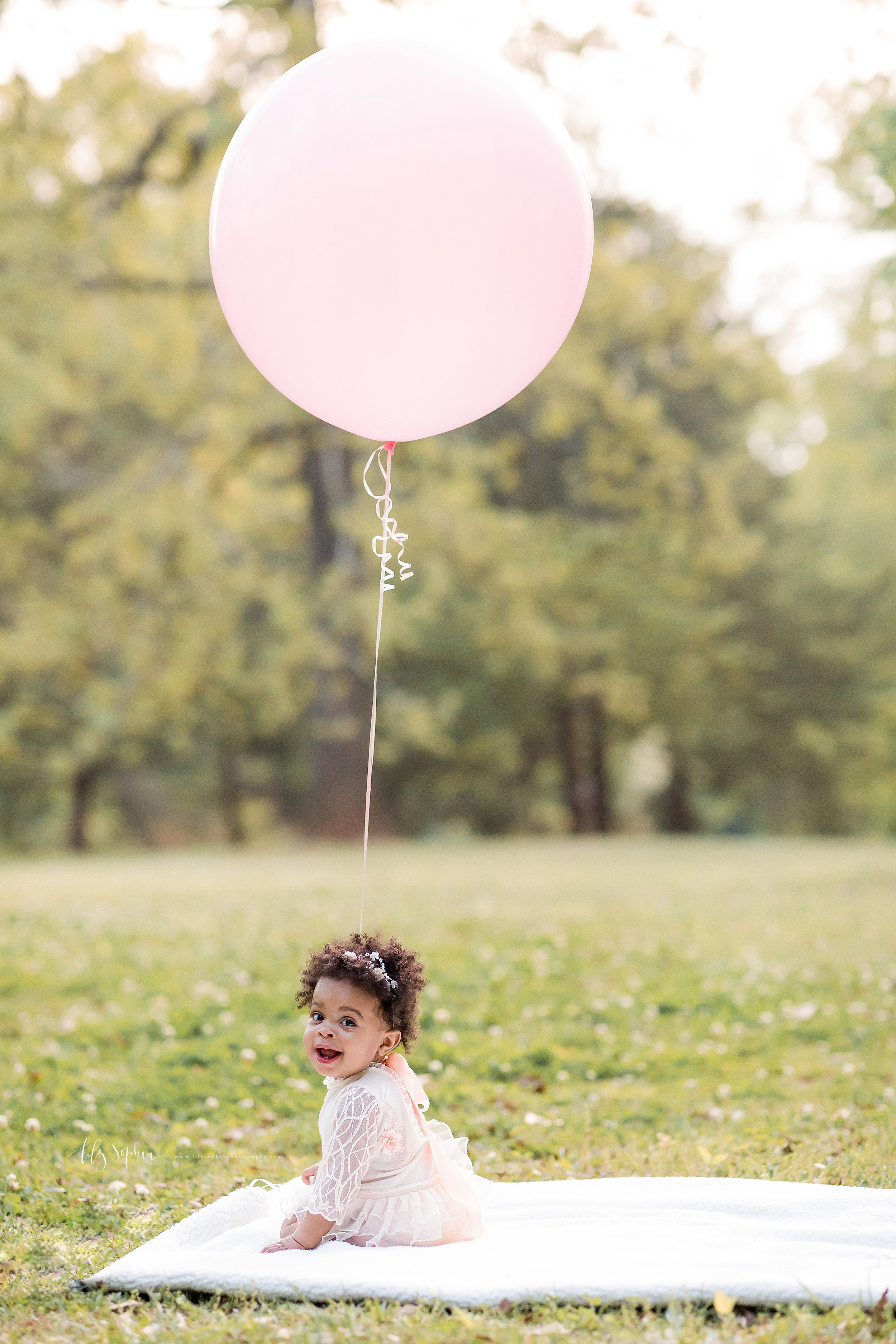 Image of an African-American one year old sitting on a white blanket in a park in Atlanta while holding a large pink balloon for her first birthday.  The little girl is turning her head over her left shoulder as the balloon looms above her head.