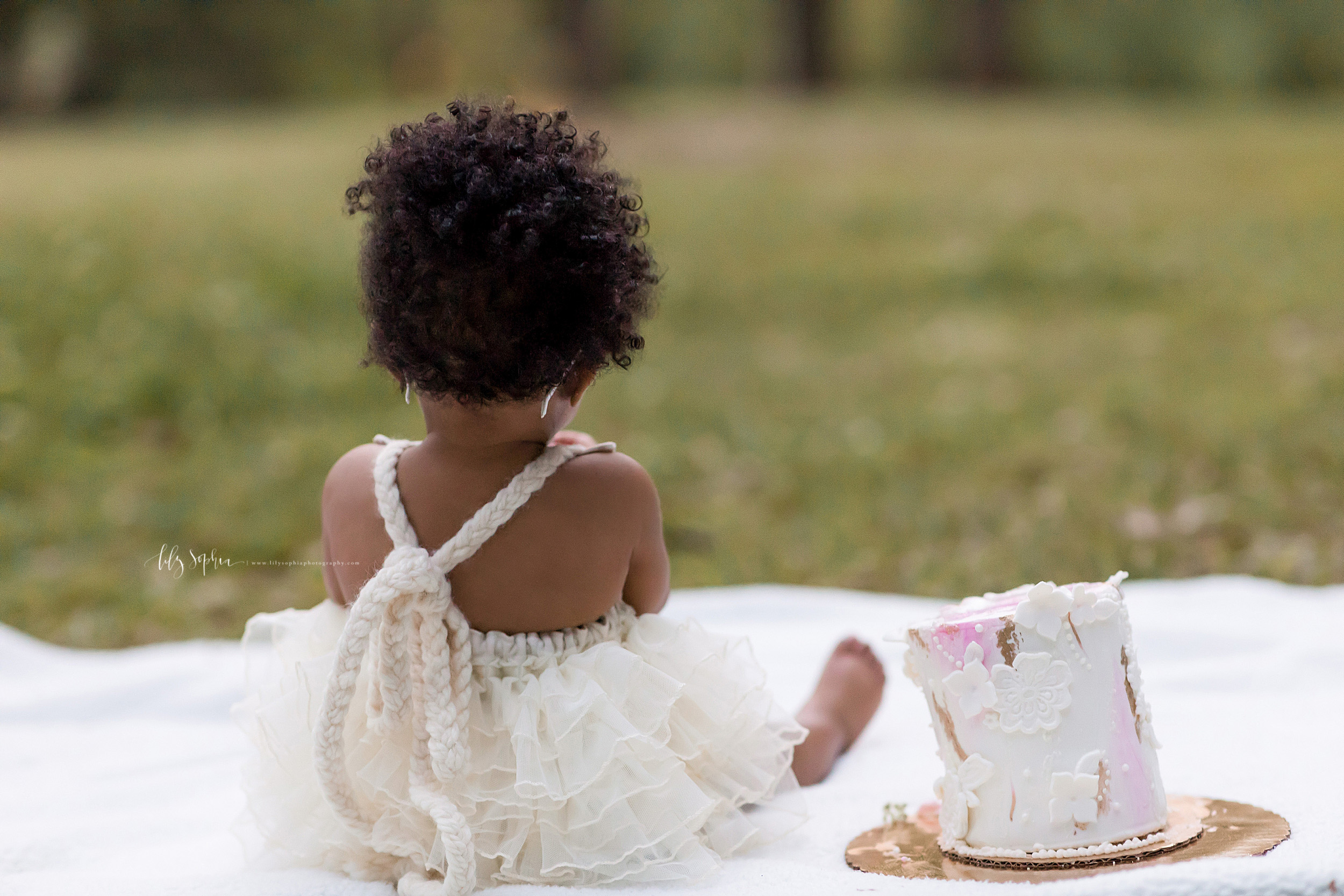Photograph of the back of an African-American one year old in an Atlanta park at sunset.  The little girl is wearing a cream backless dress with chiffon ruffles and a braided tie as she sits on a white blanket.  Next to her is her birthday cake.
