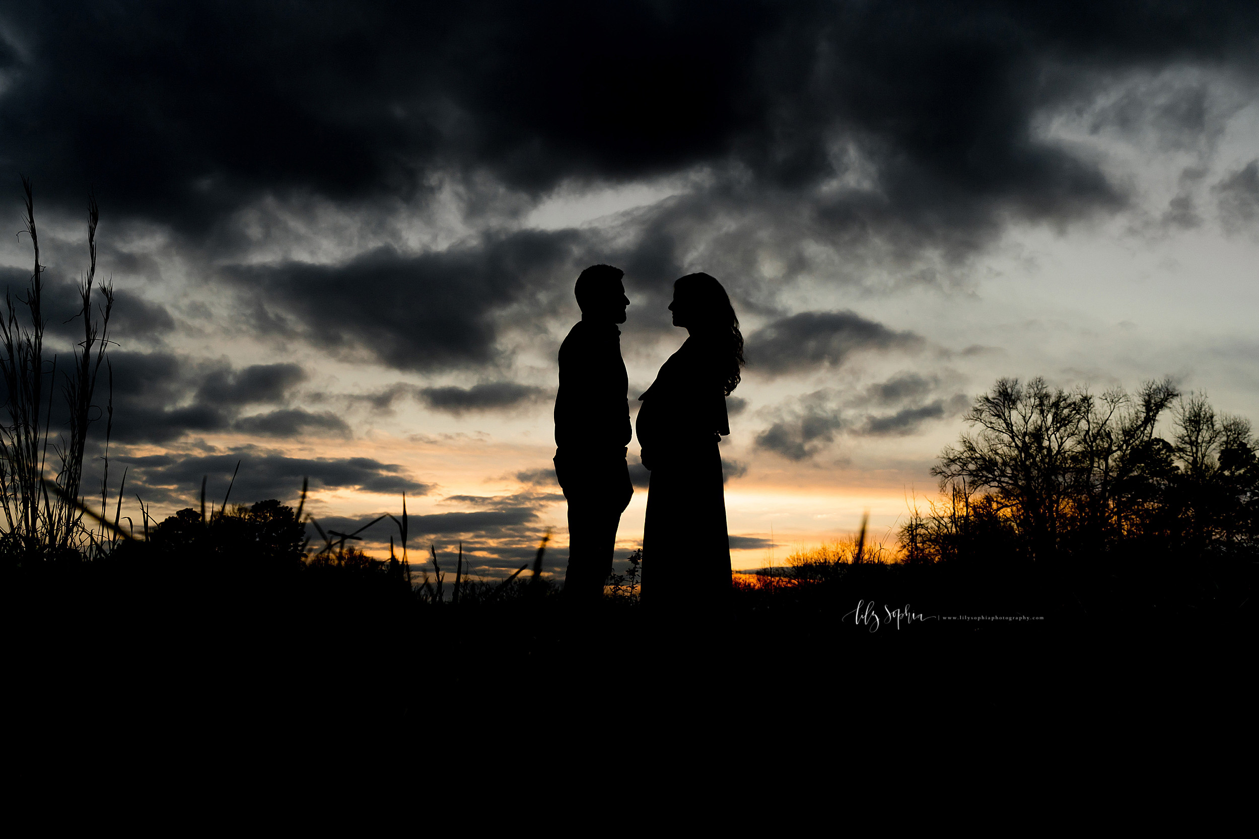 Silouhette profile image of an expectant couple as the  sun sets in Atlanta.
