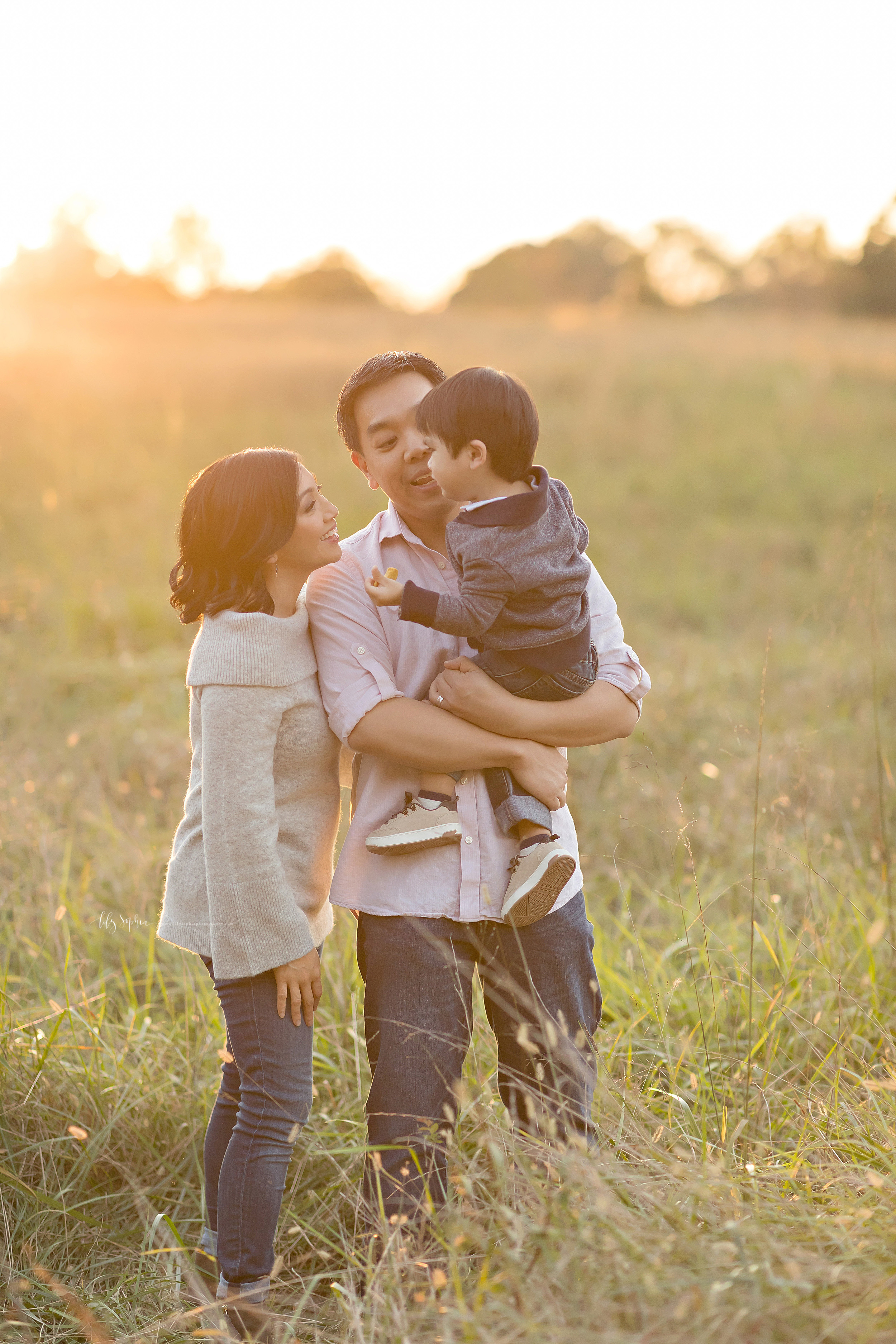 Photograph of a happy Asian family of three in a field at sunset in Atlanta.  The father is holding his two year old son in his arms and mom is looking at the two year old as she stands next to dad's right side.