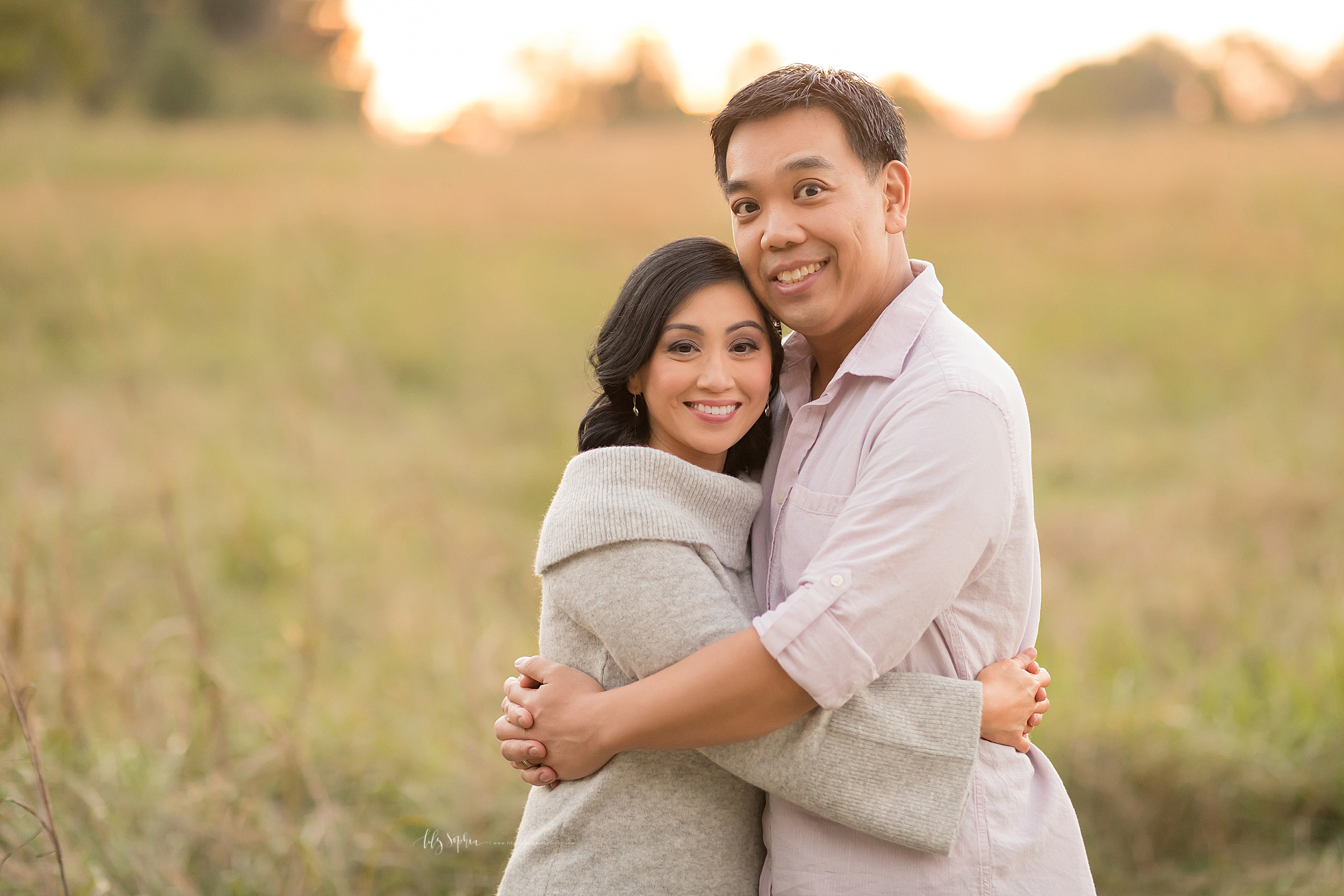 Image of a happy Asian couple hugging one another in a field at sunset.  The husband and wife are standing facing one another and they both have their arms around each other's waists.  The wife is wearing a gray cowl neck sweater with bell sleeves and blue jeans.  The husband is wearing a roll tab pink cotton button down shirt and blue jeans.