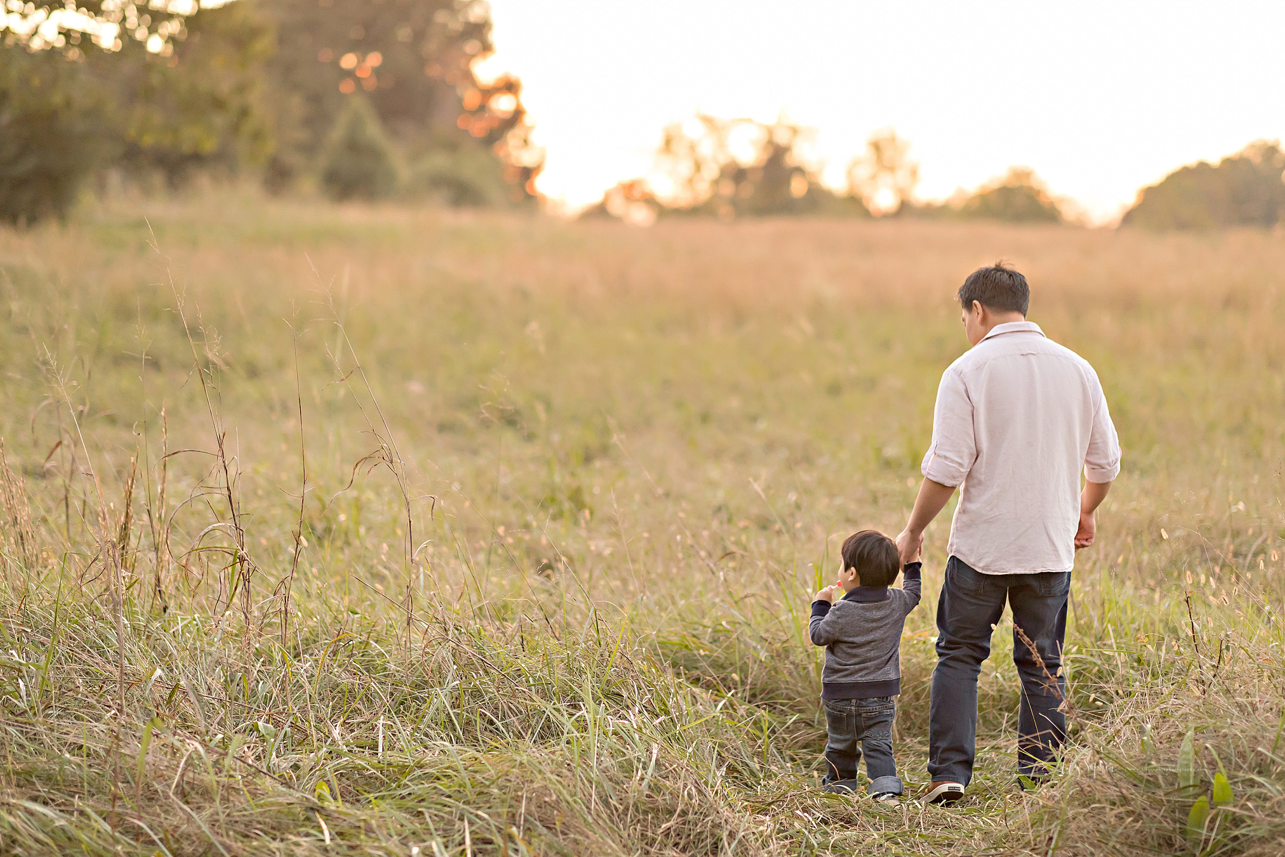 Image of an Asian father and his young son as they walk up a hill in a field at sunset.