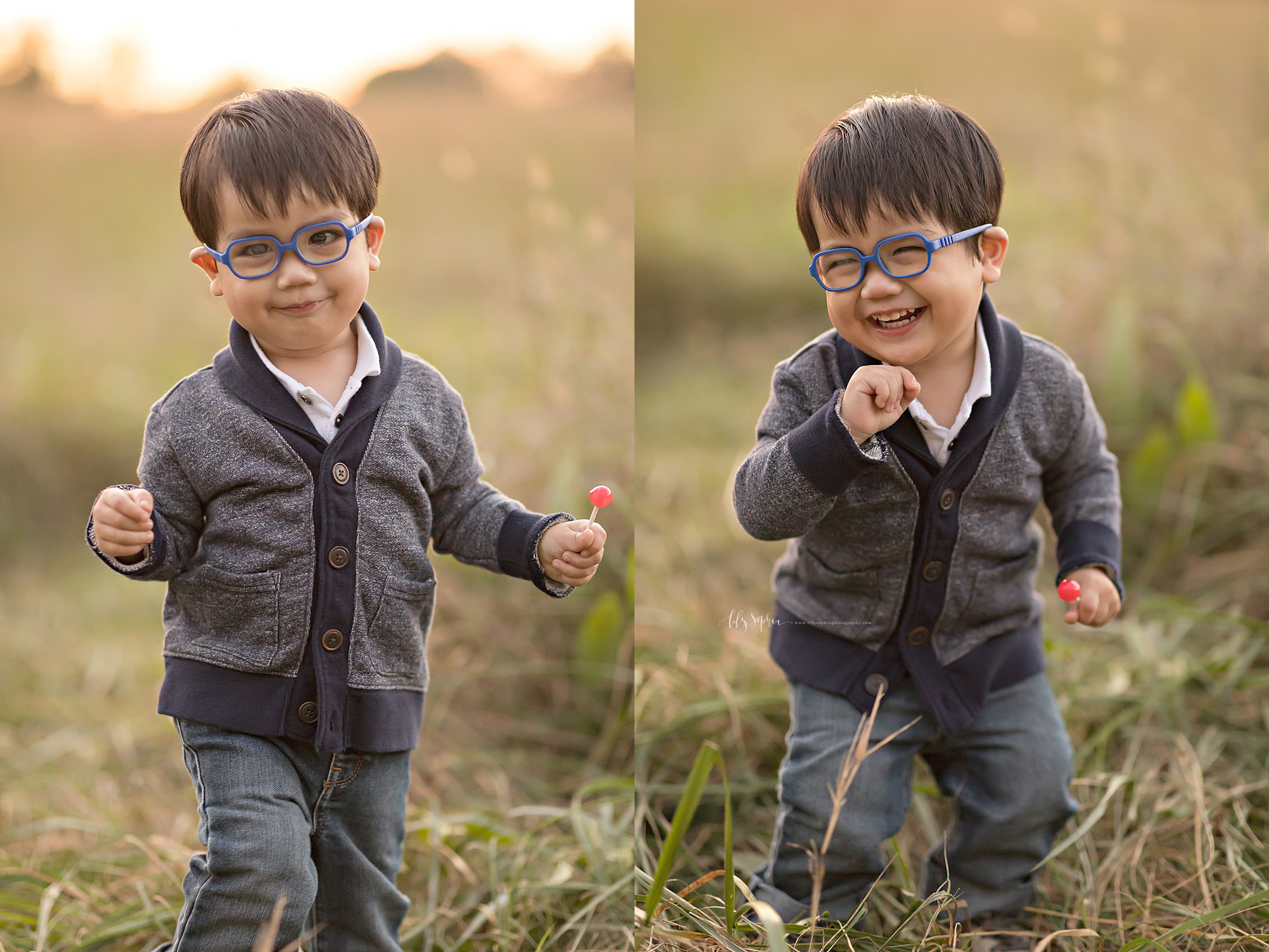 Image of an Asian two year old boy enjoying a lollipop in an Atlanta field at sunset. The little boy with blue glasses is wearing a gray button down sweatshirt with navy blue trim and two pockets on the front over a white polo shirt and blue jeans. He is holding a pink lollipop in his hands. He is smiling in one of the pictures and giggling in the other, so you can see his toothy smile.