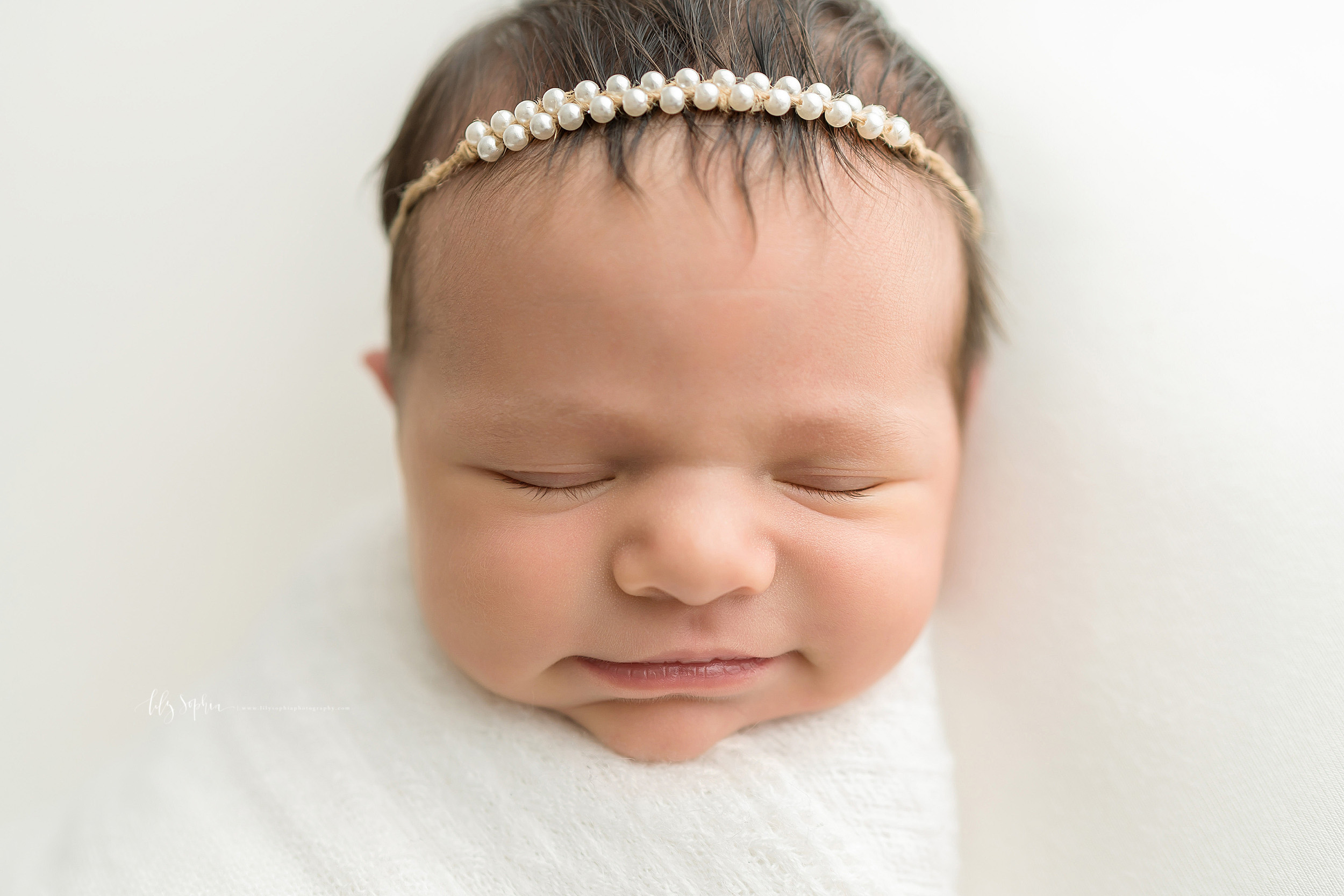 Photo of a smiling newborn as she sleeps in an Atlanta studio.  She is wearing a double strand of pearl headband in her brown hair and is wrapped to her neck in a soft white blanket.