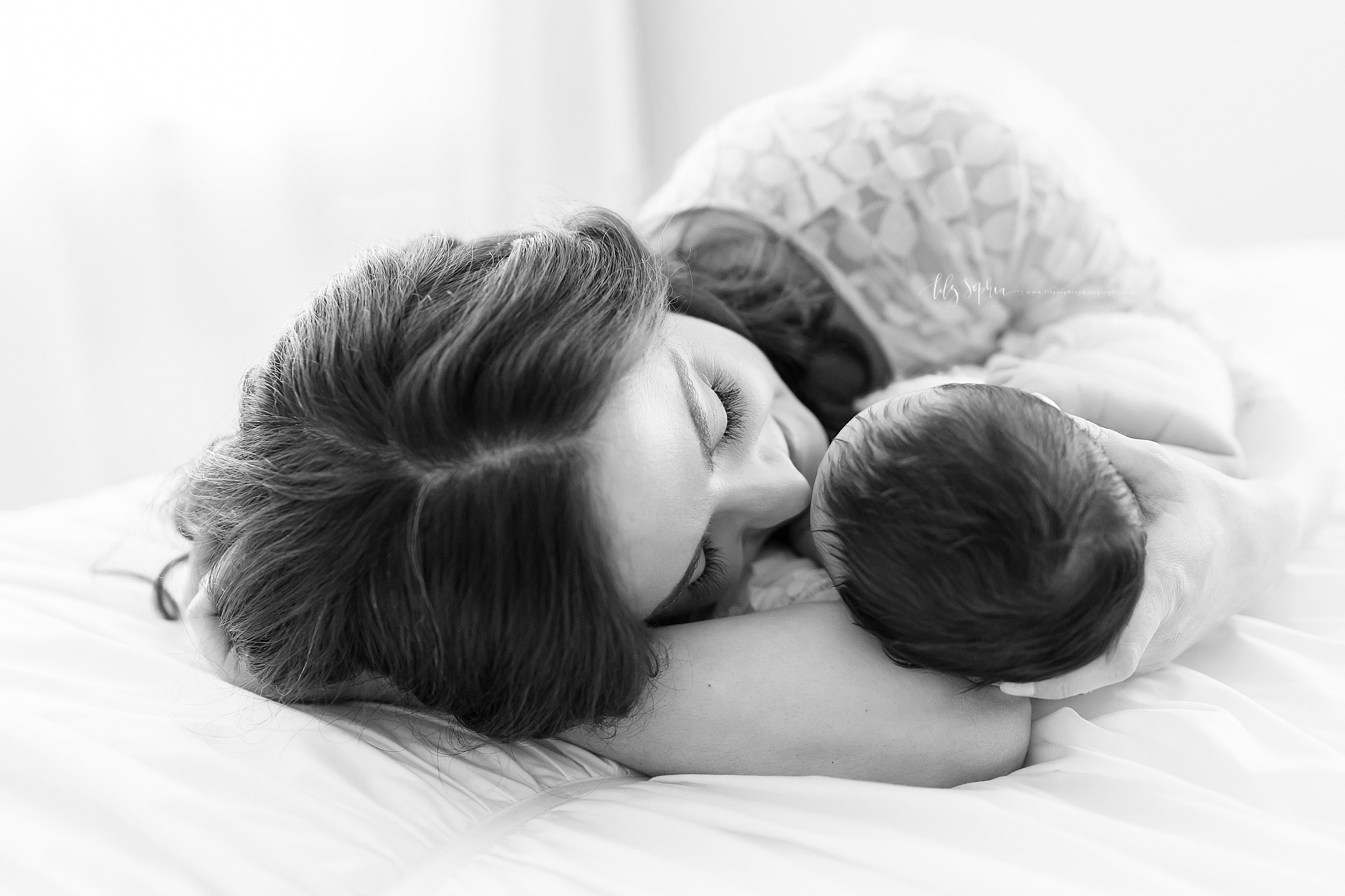 Black and White photograph of a newborn baby girl and her mom laying on a bed. The two are face to face with the baby laying on her mother's bent right arm as natural light flows in a window.