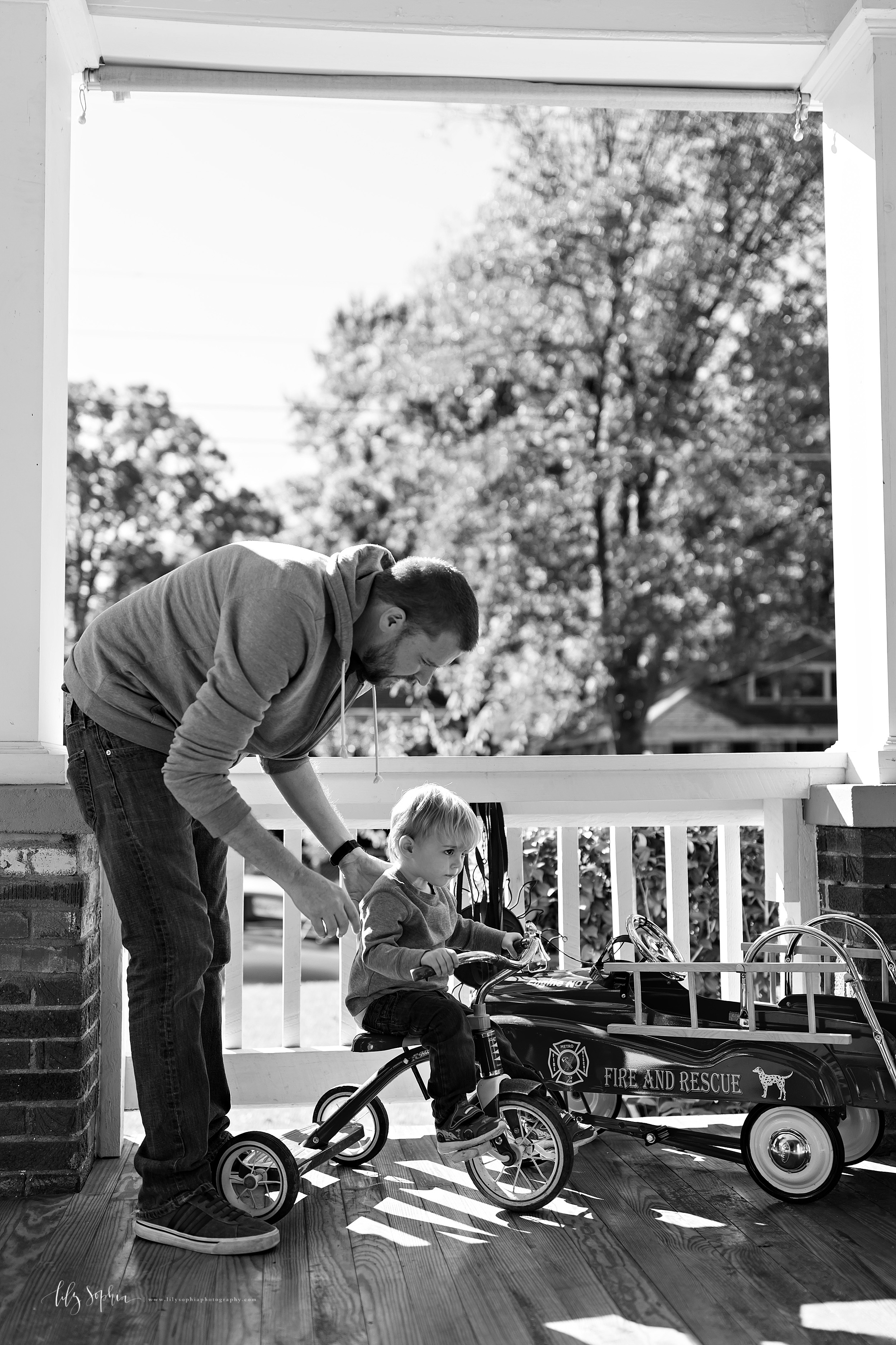 Black and white lifestyle photo of dad and his toddler son on their porch in Adair Park.  Dad is wearing a hooded sweatshirt and jeans.  His son is wearing a long-sleeved henley and jeans.  The toddler is seated on his tricycle learning how to ride.  The photo was taken by Lily Sophia Photography in natural light.
