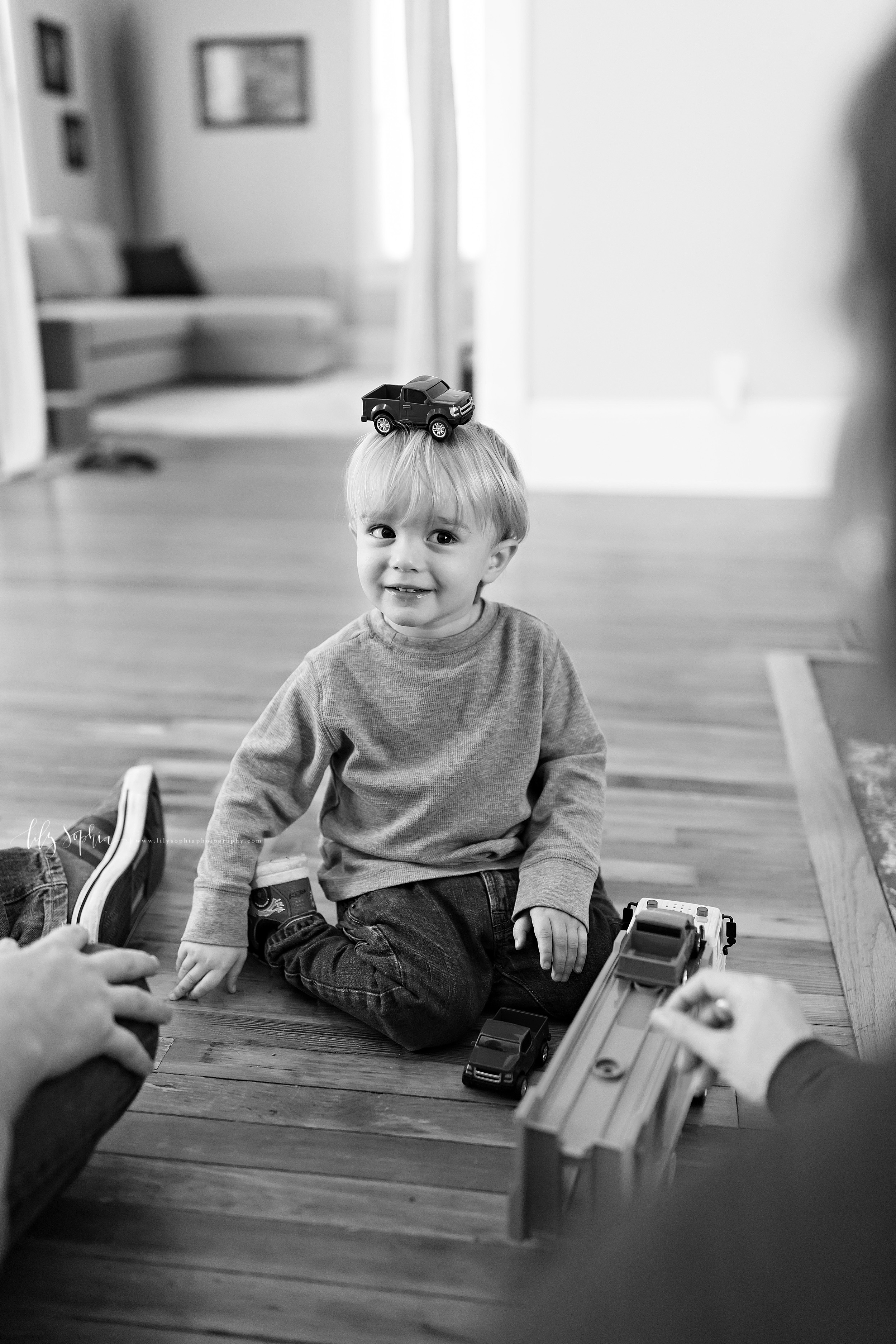 Black and white lifestyle photo of a family of three as they play with cars and trucks on the floor of their home.  The blond toddler balances a truck on his head.