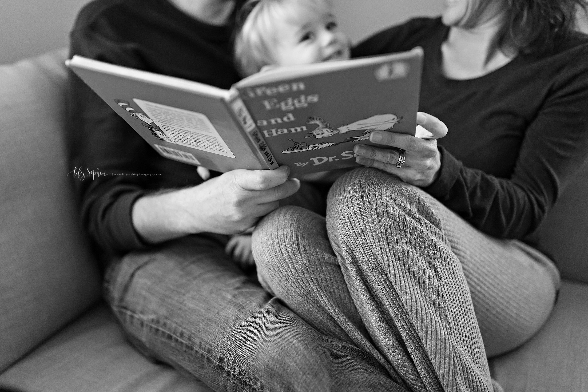 Black and white lifestyle photo of a family of three sitting on their couch reading a Dr. Seuss book together.