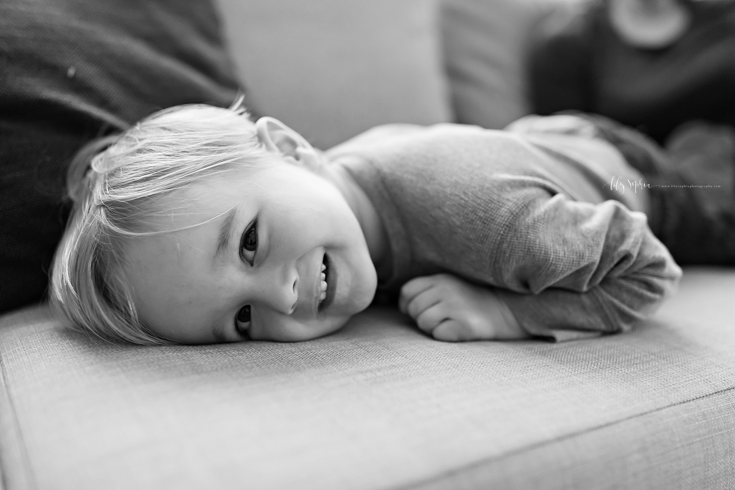 Black and white lifestyle photo of a smiling toddler boy as he lays face down on his couch at home.  He  is smiling as he looks over his left shoulder and has his left hand and arm under him.